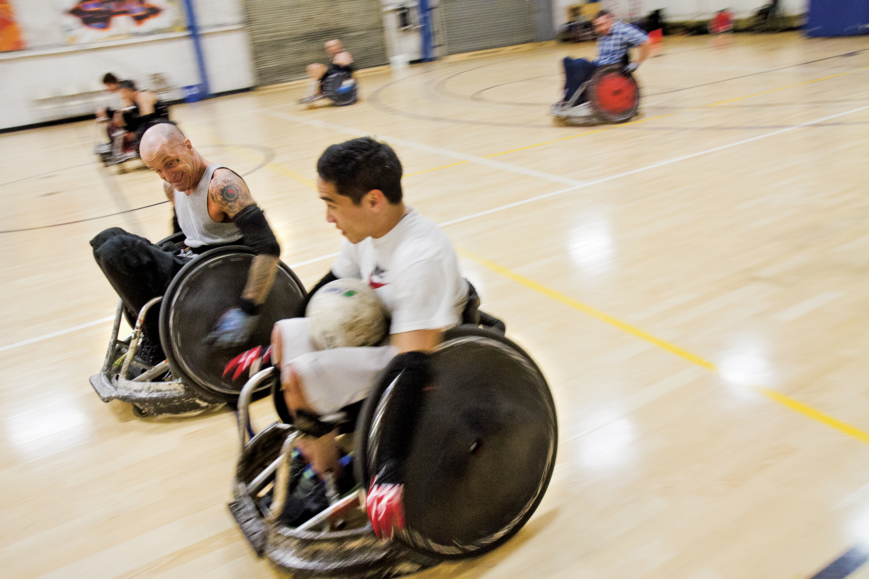 Paraplegic rugby player Scott Pope tries to get the ball from Steven Toyoji during a scrimmage at the Riekes Center.