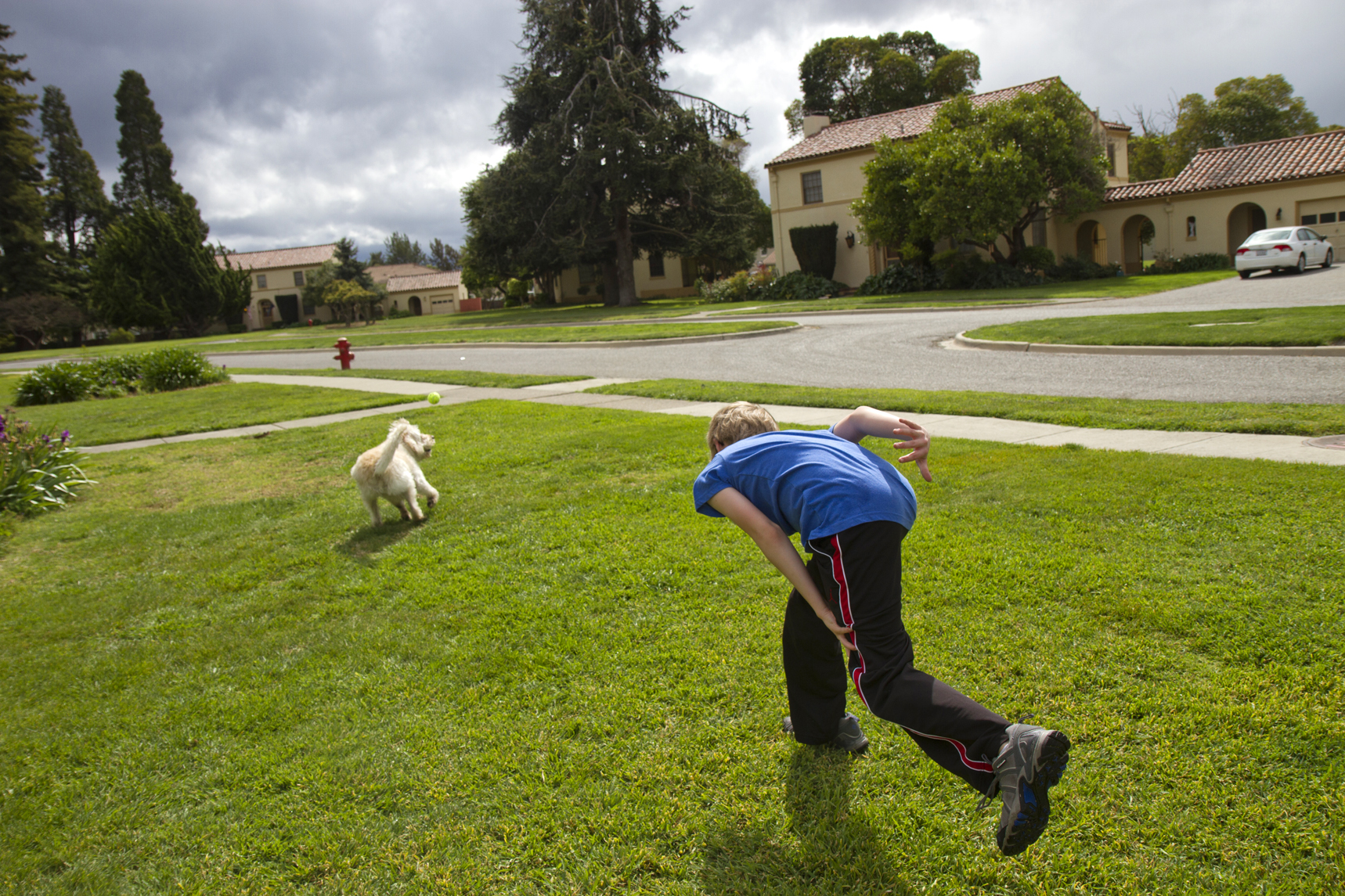 A boy plays fetch with his dog in his front yard, at Moffett Field base housing, on March 25, 2014.