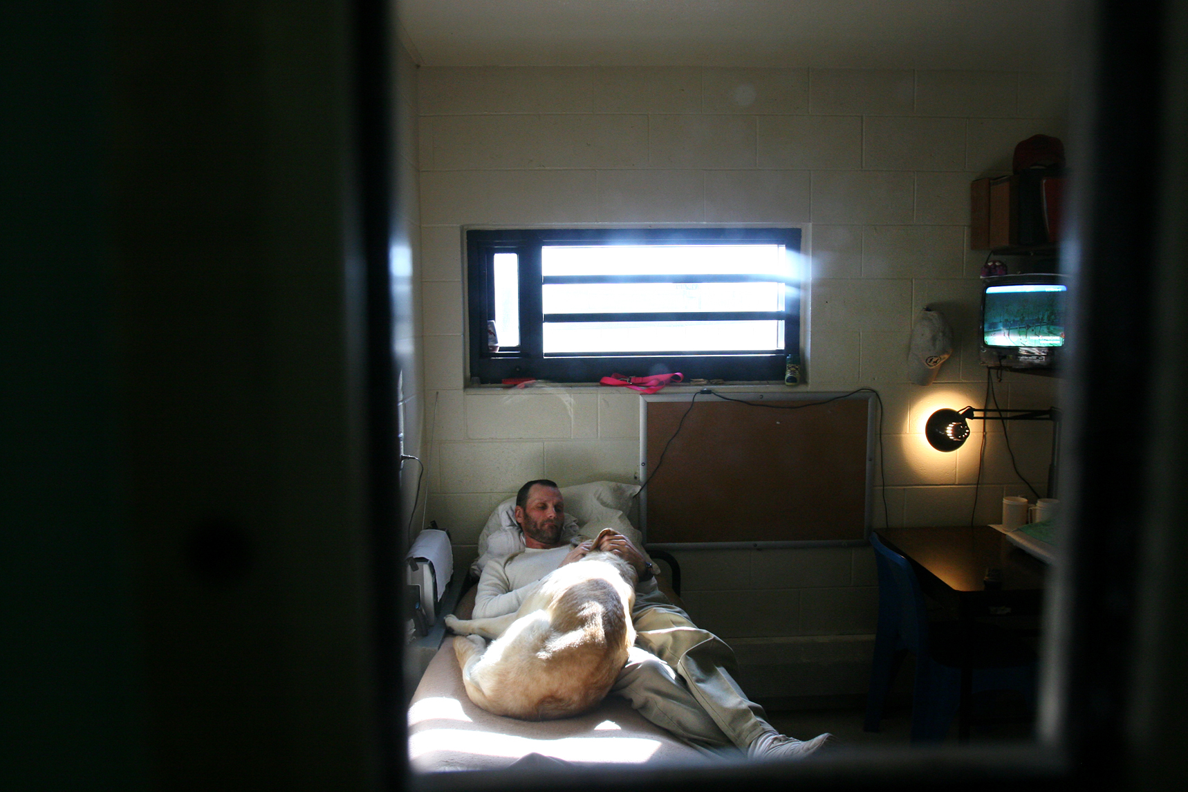 Earl Russell, 43, lays with his dog Riba in his single cell during midday in the Nebraska State Penitentiary.He says Riba's unconditional love has helped him cope with his recent medical conditions and denial of parole.