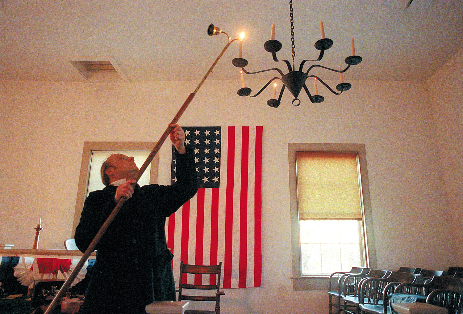 Robb Roper, a volunteer at the Mount Pulaski State Historic Site, lights candles during a open house and celebration of Lincoln's Birthday. Rich Saal/The State Journal-Register