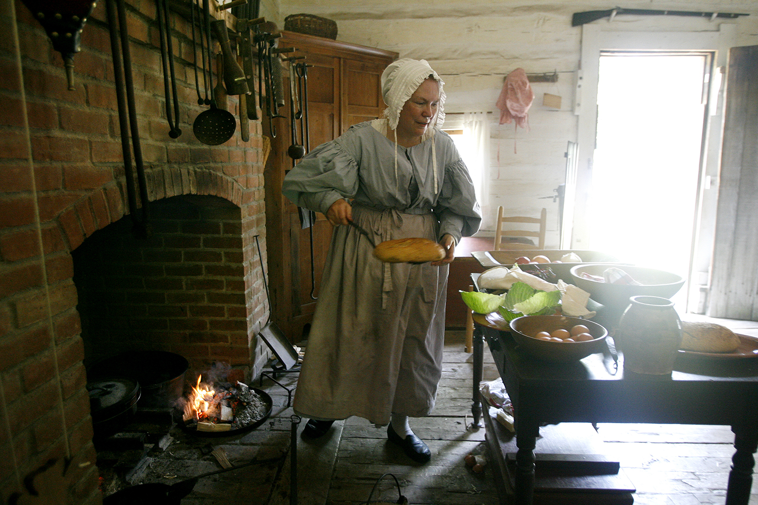 """Carol Ortery of Galesburg removes a warm loaf of wheat bread, or """"cake"""" as it was referred to, from the open hearth fireplace. Having fresh wheat to make bread was considered a treat for residents of New Salem. Ortery also was preparing steamed duck and chicken stuffed with onion, cloves and cabbage. File/The State Journal-Register"""