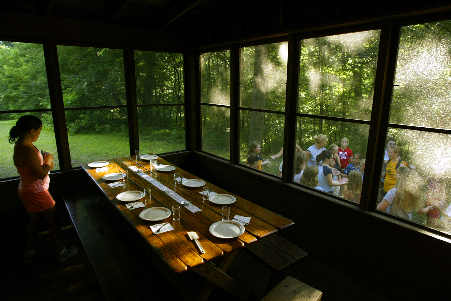 A table is prepared for dinner at Camp Widgiwagan as other campers prepare for a flag ceremony outside. The camp has 67 acres of open and wooded land at Lake Springfield. Each summer, hundreds of girls attend Camp Widgiwagan and particpate in cookouts, songs, games, canoeing and swimming. Ted Schurter/The State Journal-Register