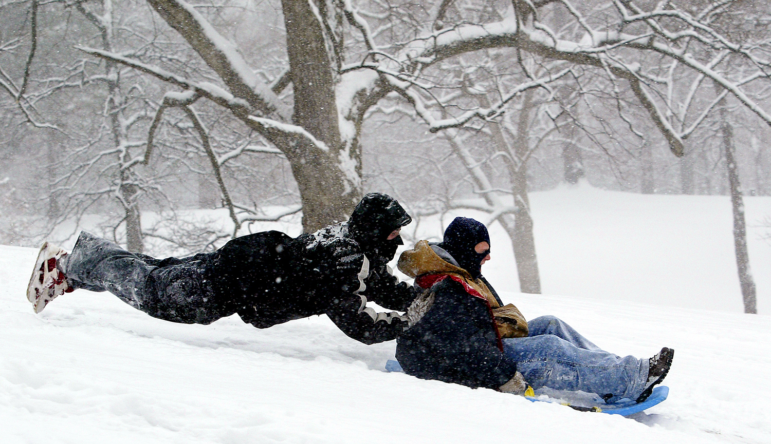 Joshua Dea, 19, gets his friend, Baron Dodd, 18, started down a hill at Douglas Park in Springfield. Jeff Thompson/The State Journal-Register