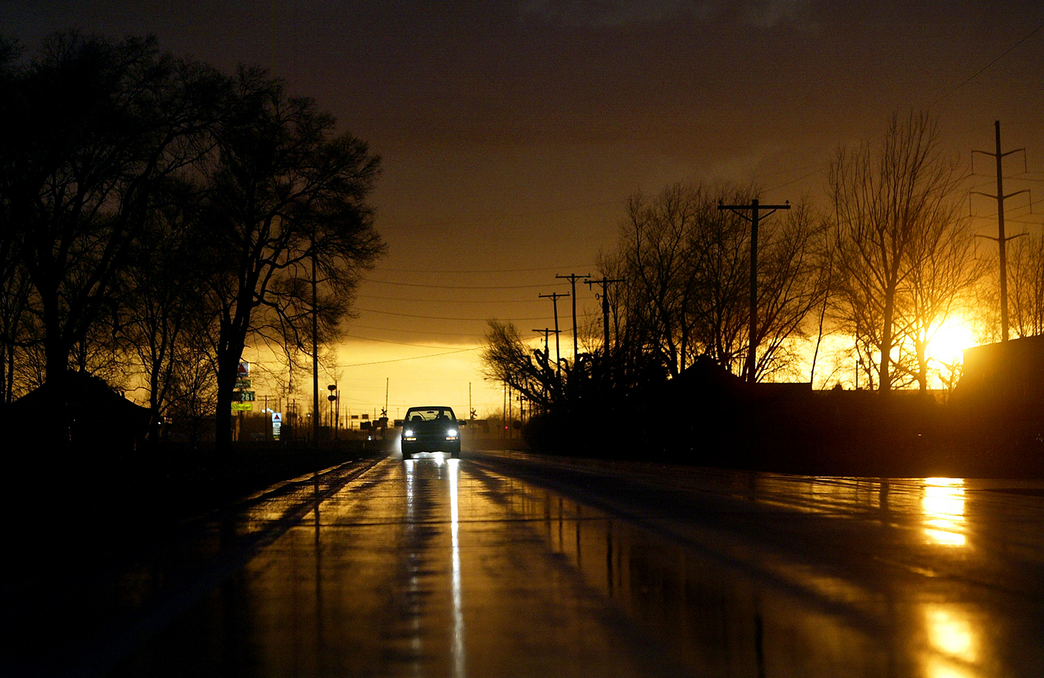 Motorists head east on Camp Butler Road as the setting sun breaks through storm clouds. Jonathan Kirshner/The State Journal-Register