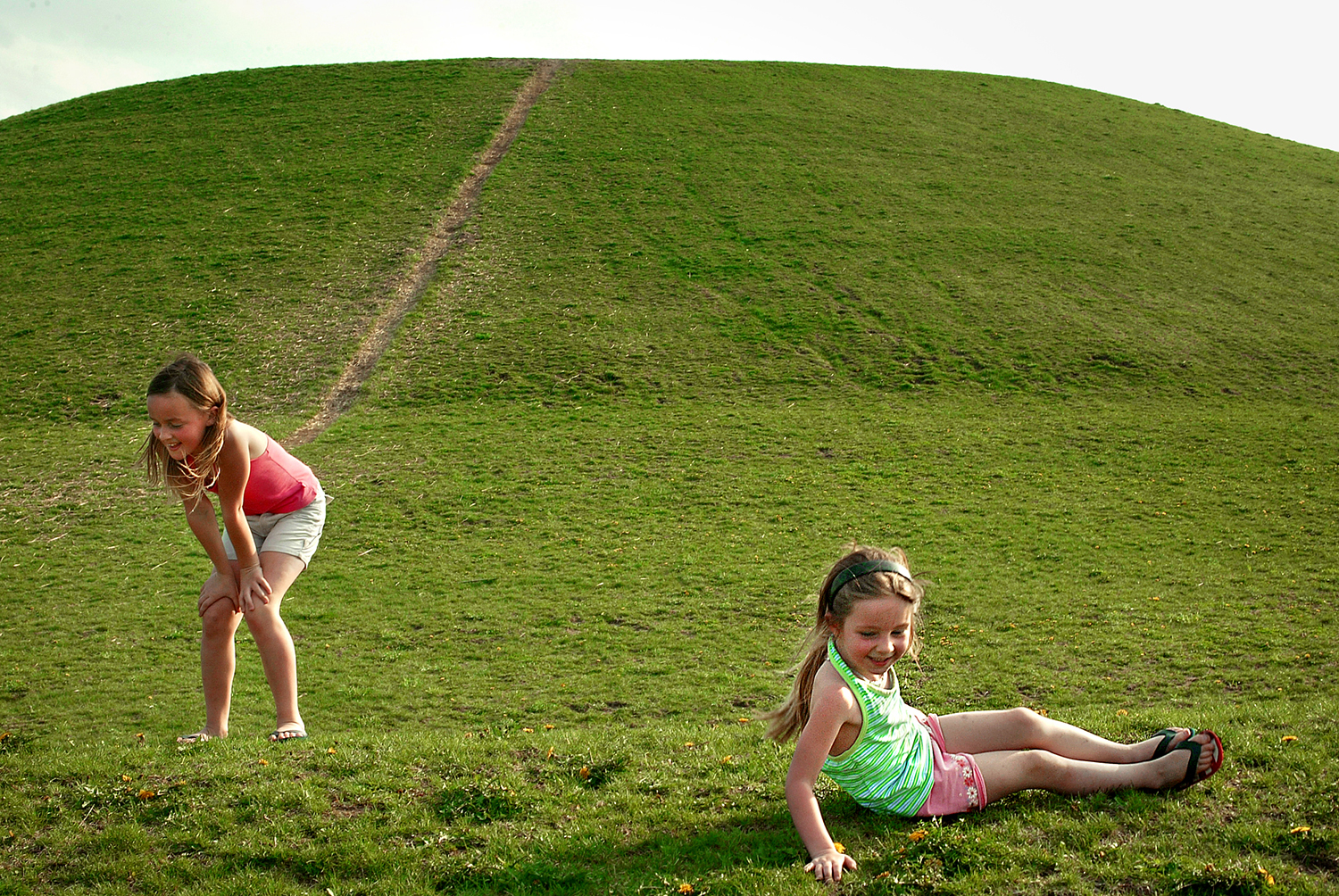 """Eight-year-old Lauren Harney catches her breath after conquering the sledding hill and rolling back down with her sister Sidney, 4, at Centennial Park, Friday, April, 14, 2006. The two girls visited the park with parents Tim and Carla Harney, who both took off of work to spend time with their daughters who are on Spring Break from School. """"We had the bestest day ever,"""" Sidney added. David Albers/The State Journal-Register"""
