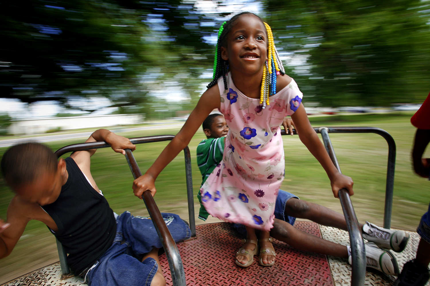 Six-year-old Keyshire Daniels, of Springfield, watches the world spin around her while playing on a merry-go-round at Comer Cox Park during the Juneteenth Celebration, Saturday, June 18, 2006. David Albers/The State Journal-Register