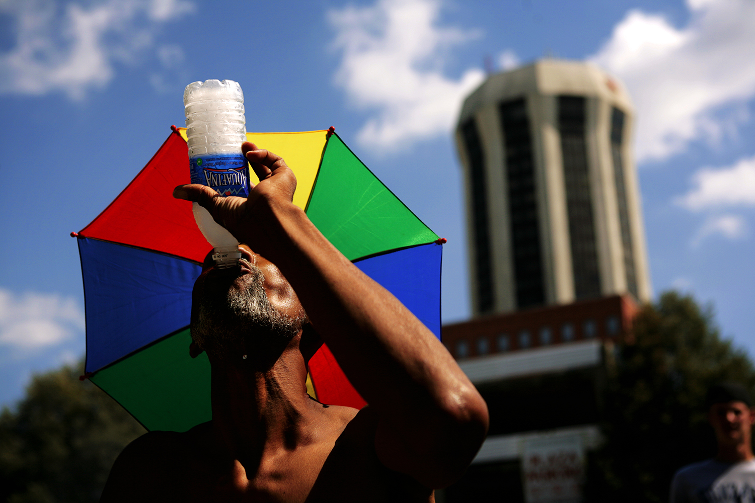 Dexter Young, of Springfield, takes a drink of water while watching his son in the Gus Macker Basketball Tournament in downtown Springfield. Max Bittle/The State Journal-Register