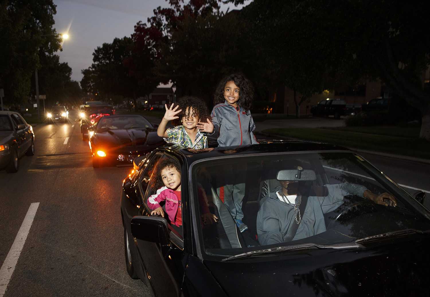 Wendy, Wardell and William Waters wave to the crowd on Sixth Street as they ride in their dad William's car during the Route 66 Mother Road Festival Friday night cruise.  Ted Schurter/The State Journal-Register