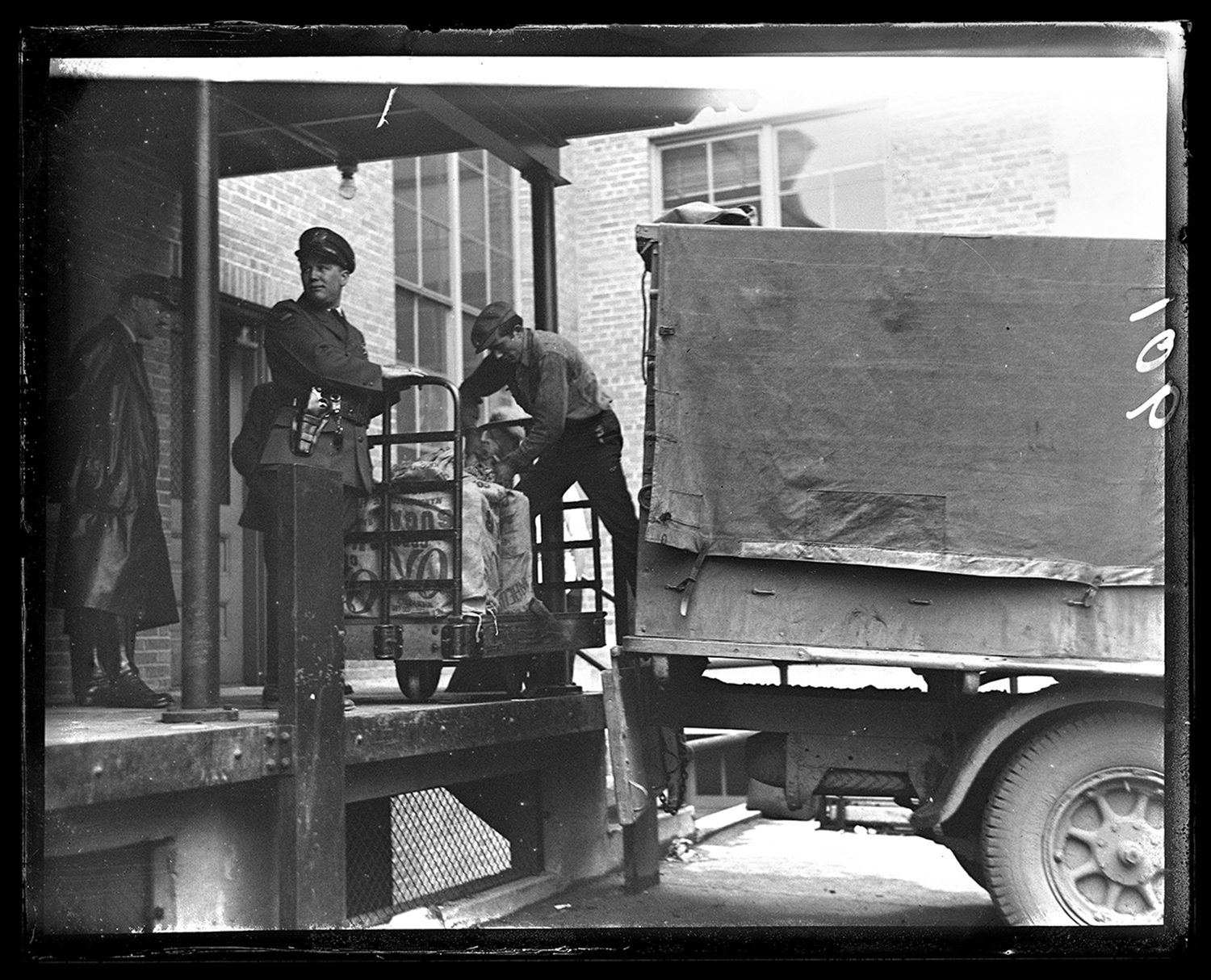 Sugar sacks loaded with gallon containers of alcohol being seized by Deputy Prohibition Administrator James A. Eaton, at loading dock of federal building Feb. 20, 1931. File/The State Journal-Register