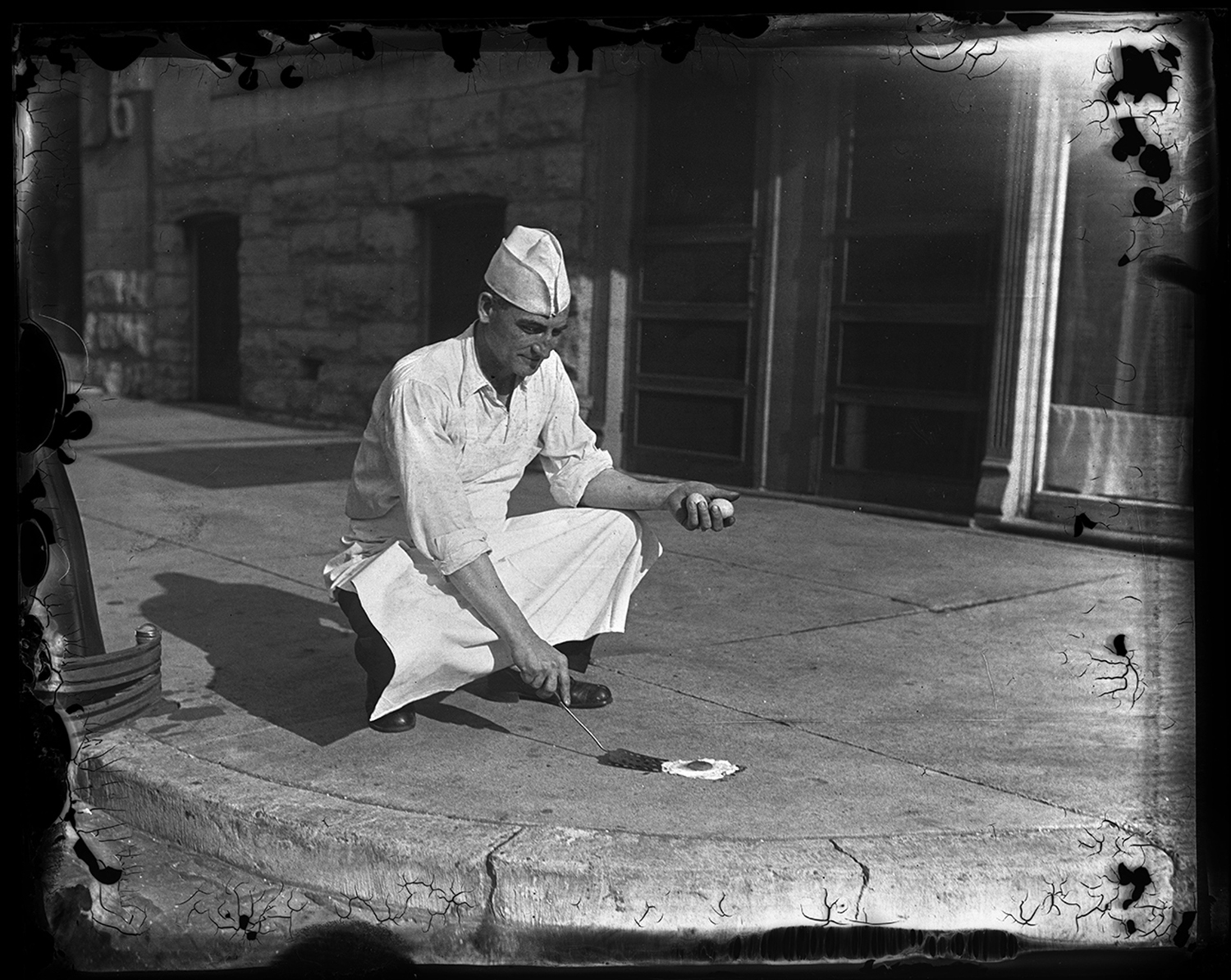 """T.M. Travis of Travis Cafeteria at 624 E. Capitol, attempting to fry an egg on sidewalk July 20, 1930. """"Heat in City Reaches 100,"""" story and photo published July 20, 1930, File/The State Journal-Register"""