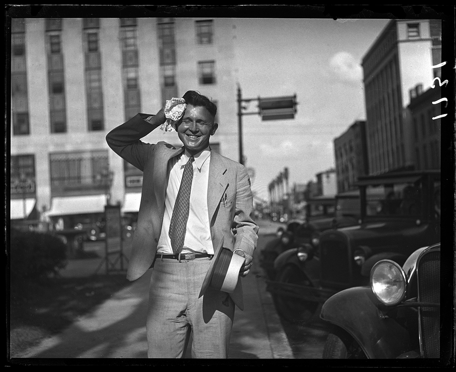Frank Dillion wipes his brow on hot summer day, July 22, 1932, walking west on Adams from Sixth Street, C.I.P.S. Building in background. The image accompanied story about severe heat wave that had begun July 12 with temperatures above 90 degrees for 10 days straight and up to 100 degrees. File/The State Journal-Register