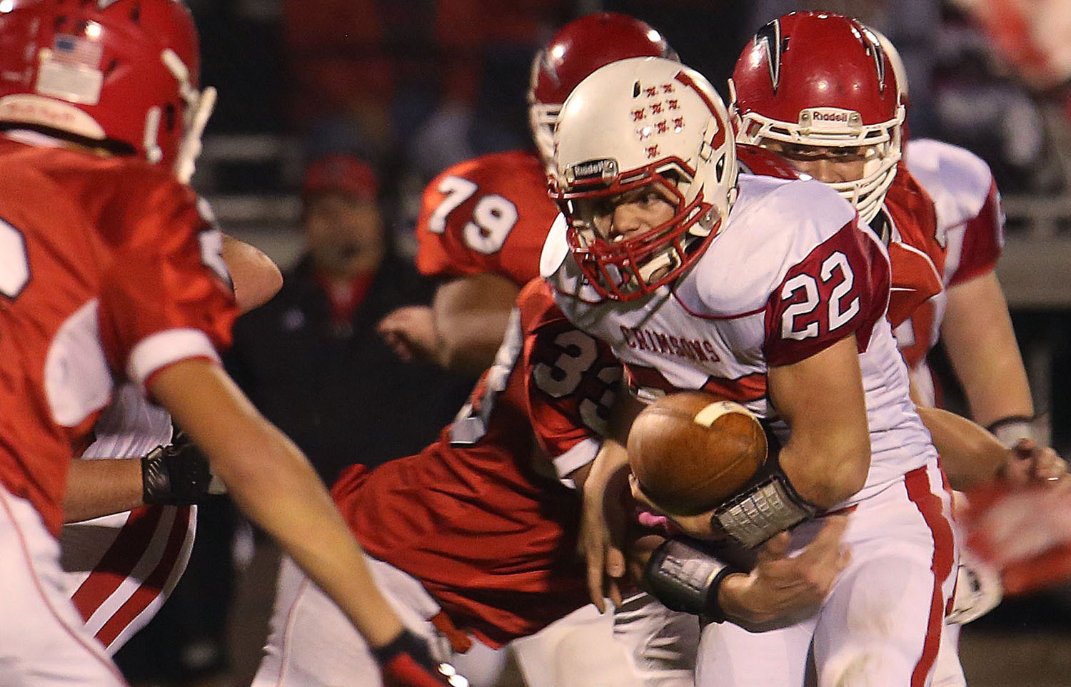 Crimsons ball carrier Matt Rooney tries to keep hold of the ball while being strong-armed by Titans defender Charlie Heminghous. The Chatham Glenwood High School Titans defeated the Jacksonville High School Crimsons 49-35 in football action on Friday evening, Oct. 24, 2014. David Spencer/The State Journal-Register