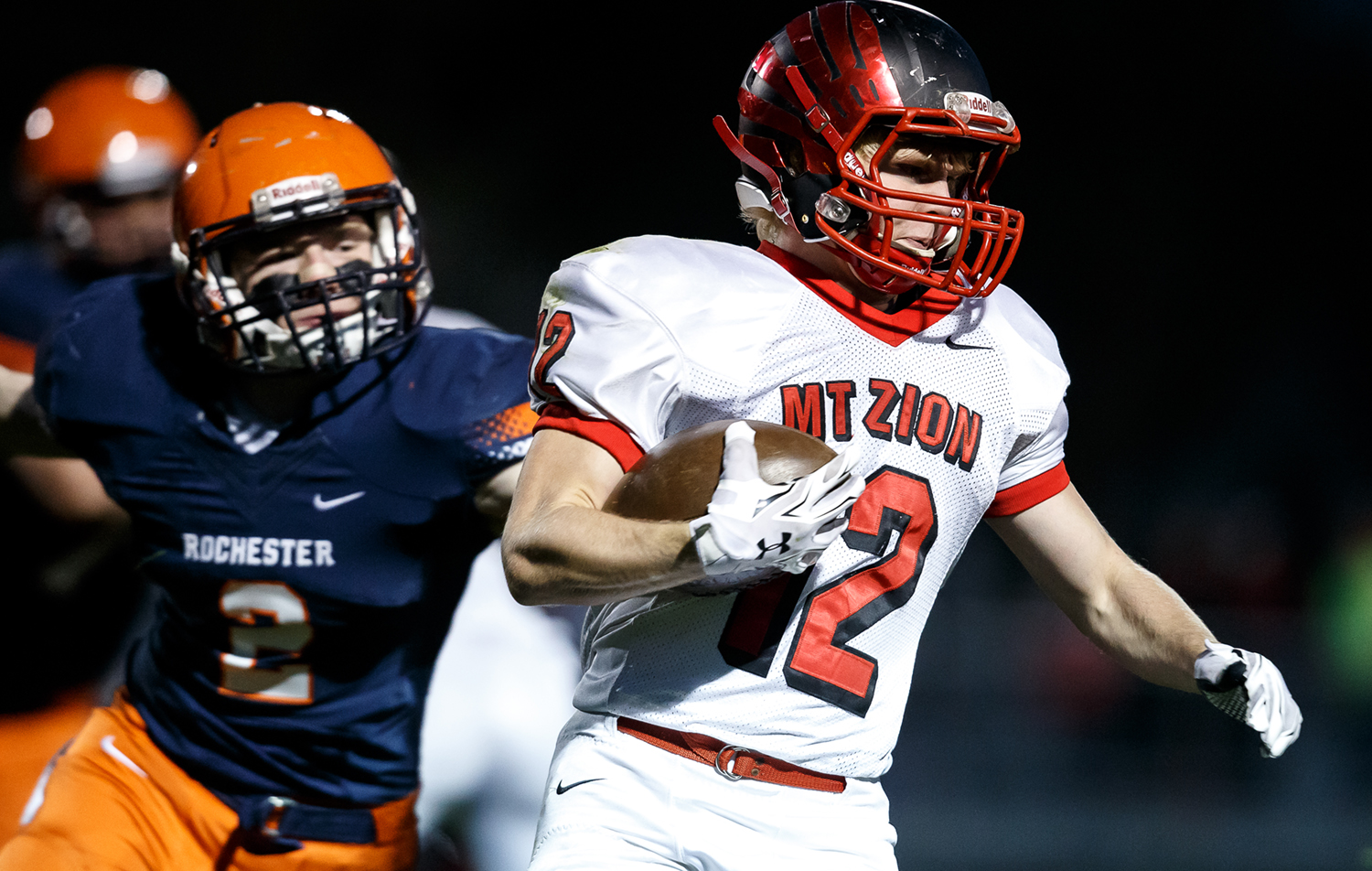 Mt. Zion's Austin Thacker (12) is caught from behind by Rochester's Eric Yakle (2) on a rush in the first half during the first round of the Class 4A playoffs at Rocket Booster Field, Saturday, Nov. 1, 2014, in Rochester, Ill. Justin L. Fowler/The State Journal-Register