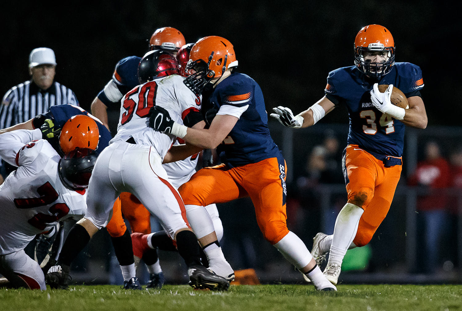 Rochester's Evan Sembell (34) stays behind his blockers as he finds a hole against Mt. Zion on a rush in the first half during the first round of the Class 4A playoffs at Rocket Booster Field, Saturday, Nov. 1, 2014, in Rochester, Ill. Justin L. Fowler/The State Journal-Register