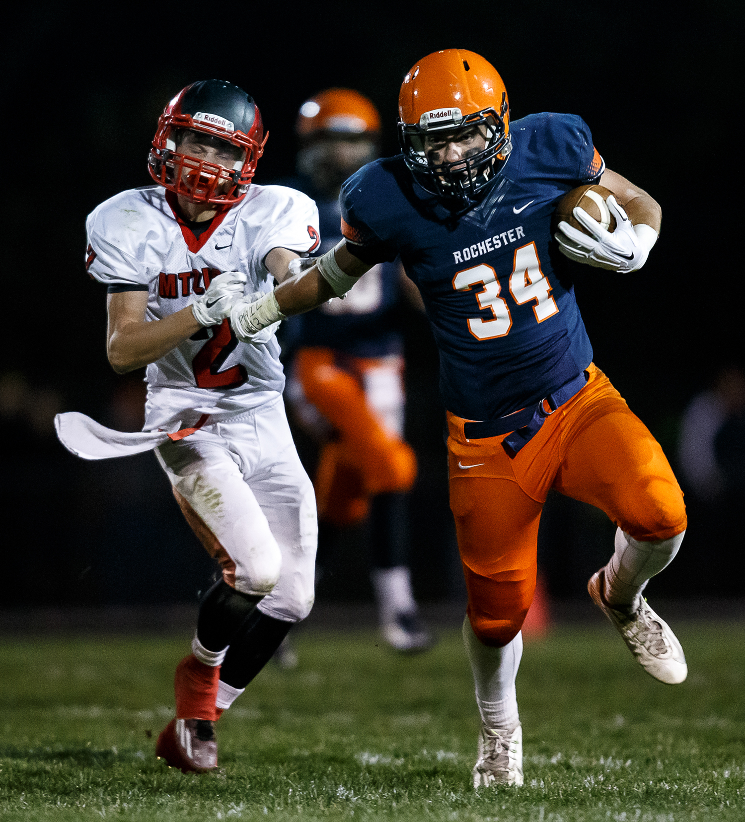 Rochester's Evan Sembell (34) puts a stiff arm on Mt. Zion's Charles Kuhle (2) to avoid a tackle on a rush in the first half during the first round of the Class 4A playoffs at Rocket Booster Field, Saturday, Nov. 1, 2014, in Rochester, Ill. Justin L. Fowler/The State Journal-Register