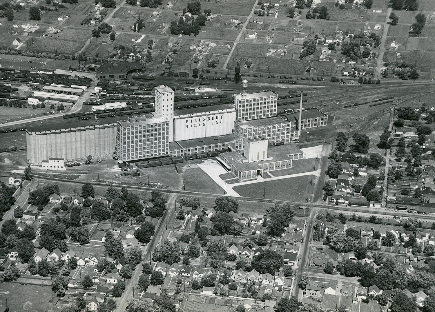 Pillsbury Mills aerial, July 1949. Photo shows new bakery mix plant, the smaller building in the corner of the triangle. Flour is fed through pneumatic tubes from across railroad tracks. Mercury Studios Collection/The Sangamon Valley Collection at Lincoln Library