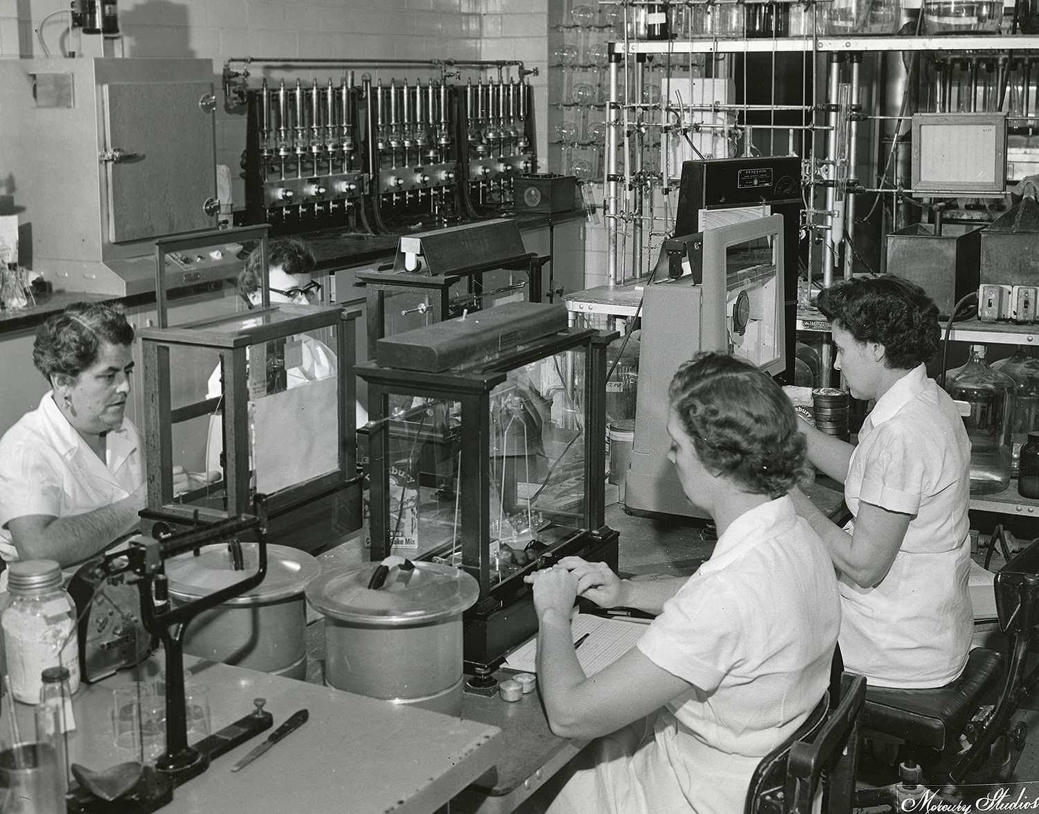 Pillsbury Mills, Sept. 2, 1955. Technicians from left, Elsie Bull, Sharon Marcellus, Pauline Rethinker and Velma Gristy in mill control laboratory. Mercury Studios collection/Sangamon Valley Collection at Lincoln Library