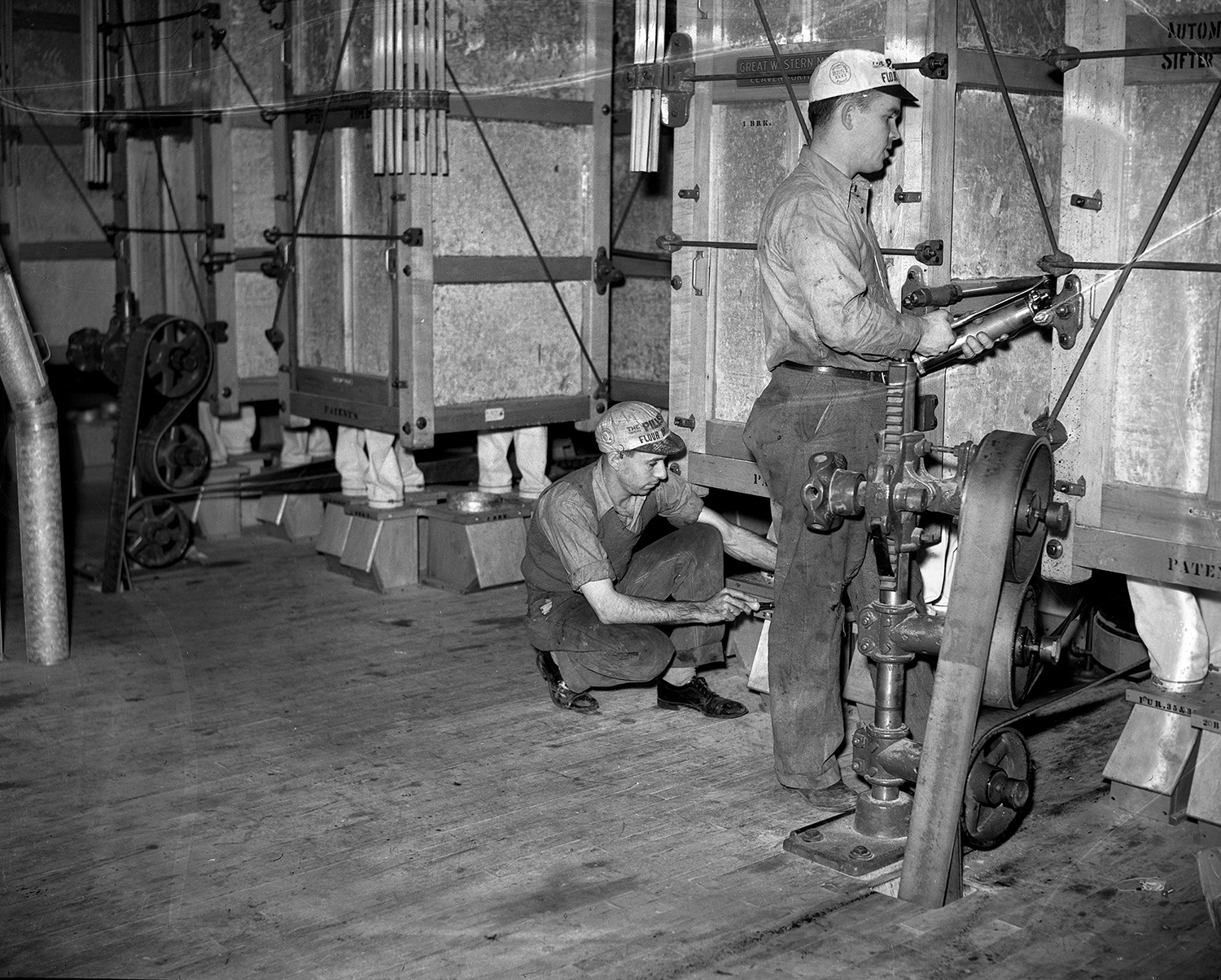 Jules Marcy, left, and John Snyder work on the flour sifters, October 1937. File/The State Journal-Register