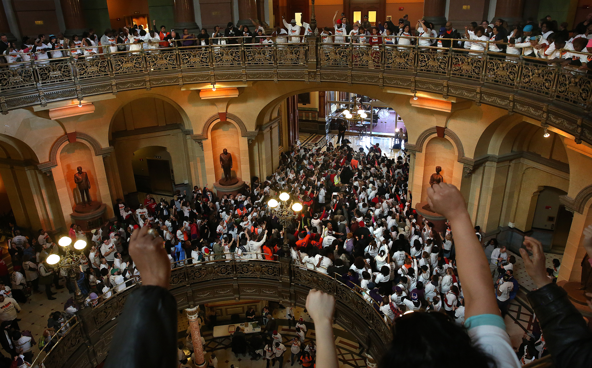 """Several thousand protestors packed the public areas and chanted against budget cuts inside the rotunda of the State Capitol building during the rally on Wed. March 11, 2015. As part of """"We Rise"""", a national day of action targeting state budget cuts, several thousand people from faith, community and labor organizations including adults, children and clergy affected by Gov. Bruce Rauner's proposed cuts gathered in Springfield to protest. The event began with a rally inside the Capitol building followed by a march to the governor's mansion where a mock """"funeral"""" for the """"99%"""" took place. David Spencer/The State Journal-Register"""