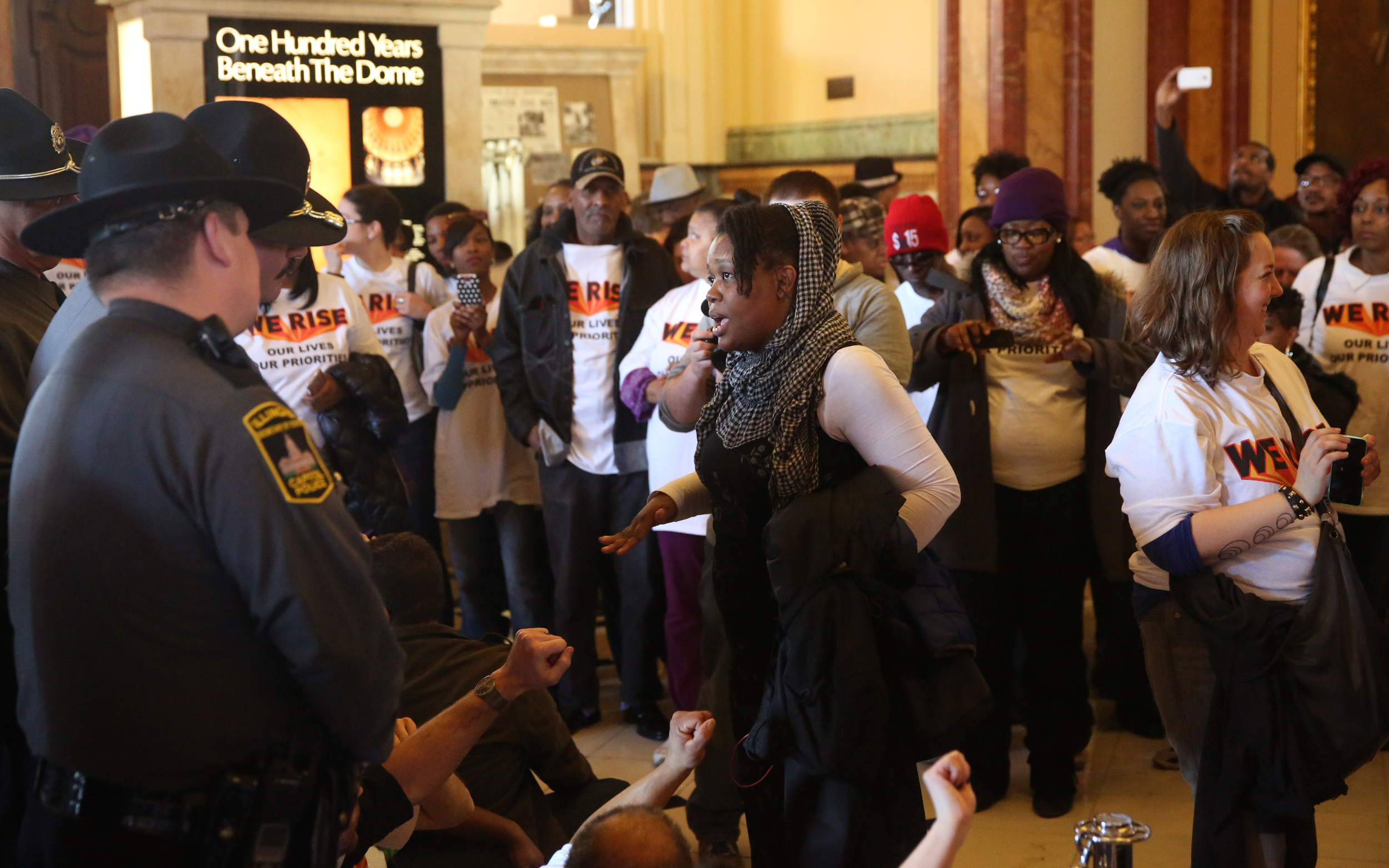 """A rally organizer speaks with Secretary of State police officers while protesters sit in front of them outside the Governor's office during an act of civil disobedience inside the State Capitol building during the rally on Wed. March 11, 2015. As part of """"We Rise"""", a national day of action targeting state budget cuts, several thousand people from faith, community and labor organizations including adults, children and clergy affected by Gov. Bruce Rauner's proposed cuts gathered in Springfield to protest. The event began with a rally inside the Capitol building followed by a march to the governor's mansion where a mock """"funeral"""" for the """"99%"""" took place. David Spencer/The State Journal-Register"""