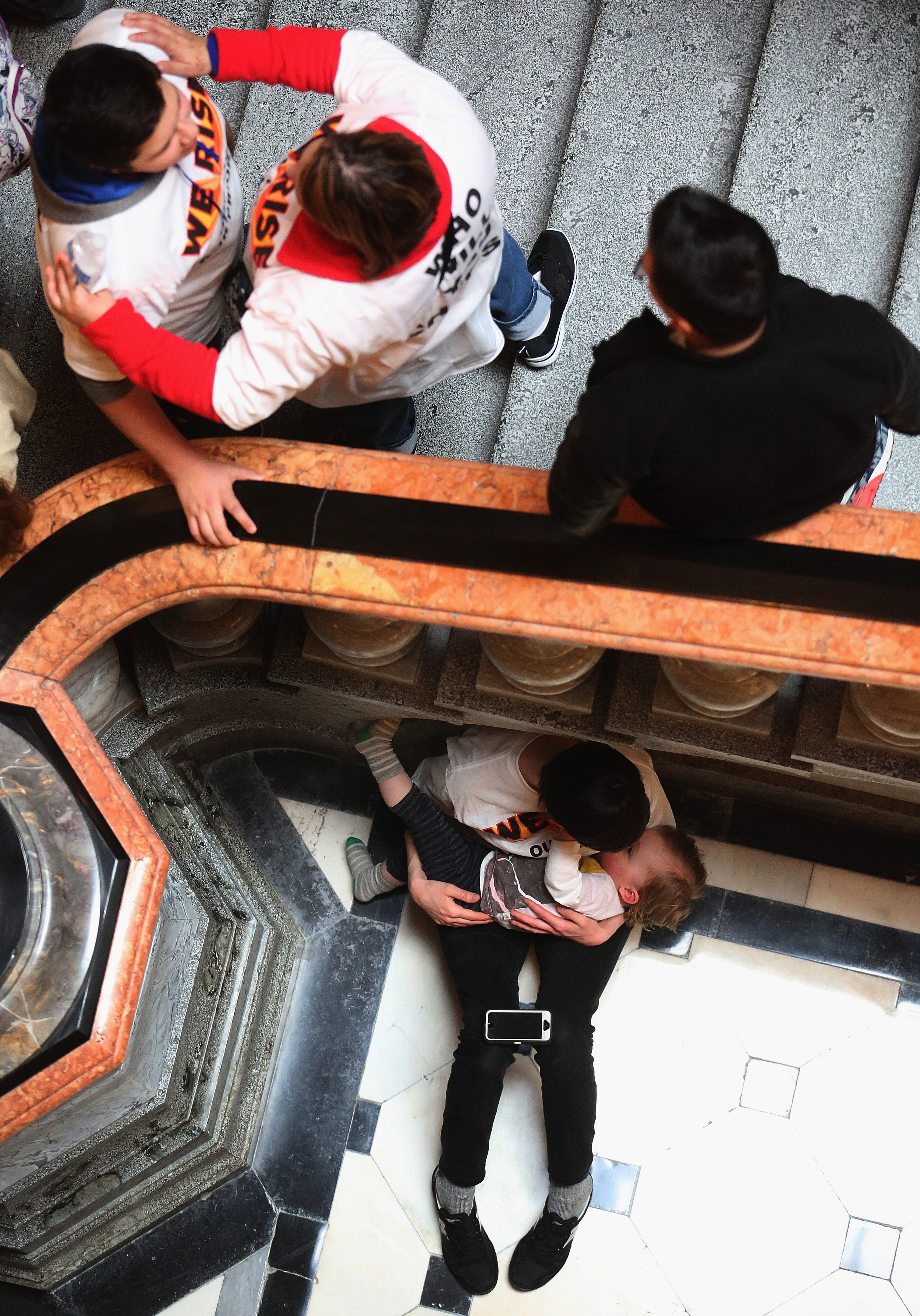 """A mother attending the rally nurses her child behind a bannister inside the State Capitol building on Wed. March 11, 2015. As part of """"We Rise"""", a national day of action targeting state budget cuts, several thousand people from faith, community and labor organizations including adults, children and clergy affected by Gov. Bruce Rauner's proposed cuts gathered in Springfield to protest. The event began with a rally inside the Capitol building followed by a march to the governor's mansion where a mock """"funeral"""" for the """"99%"""" took place. David Spencer/The State Journal-Register"""