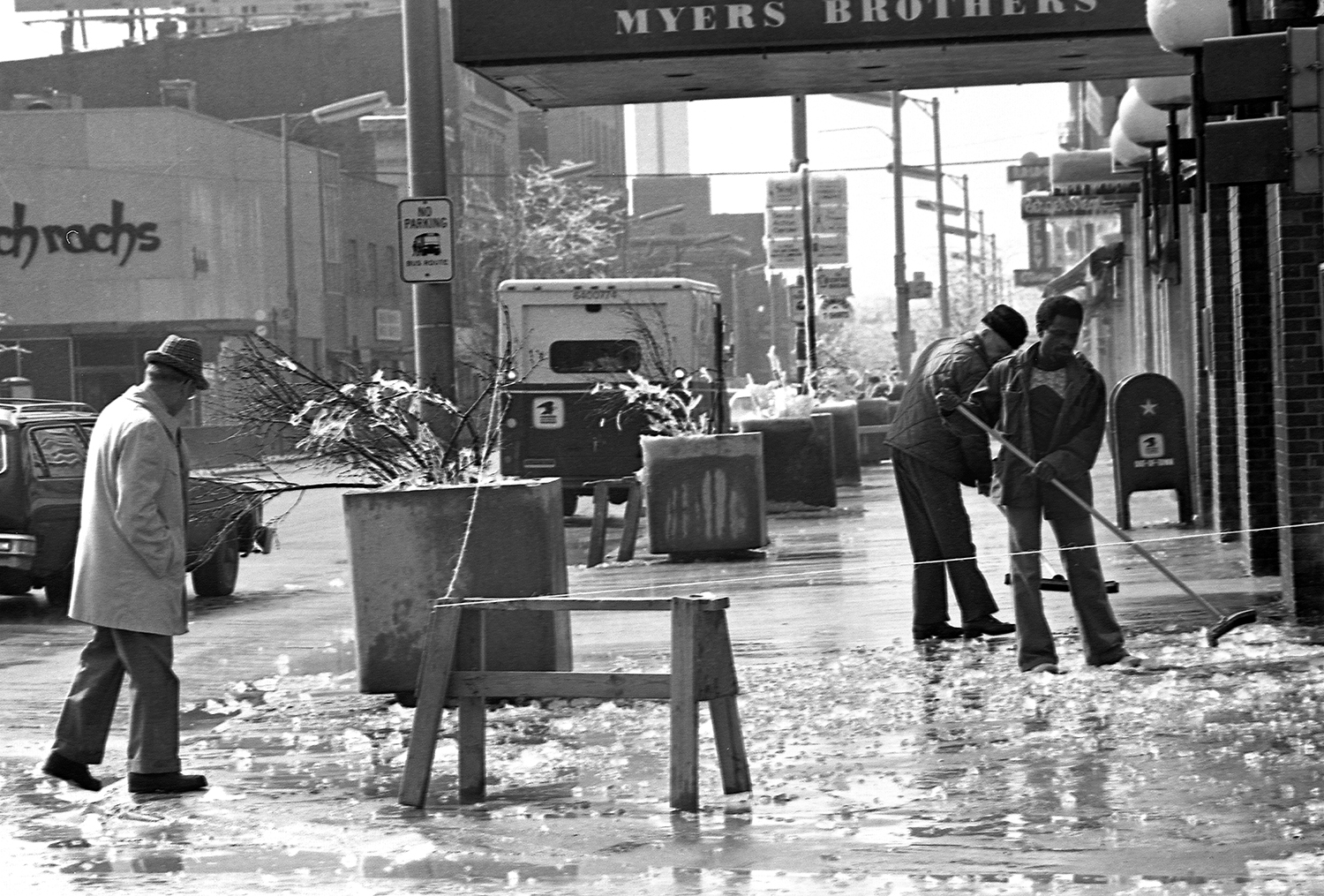 Workers clear the sidewalk of ice from that had fallen from the upper part of the Myers Bros. building on Fifth Street, March 1978.