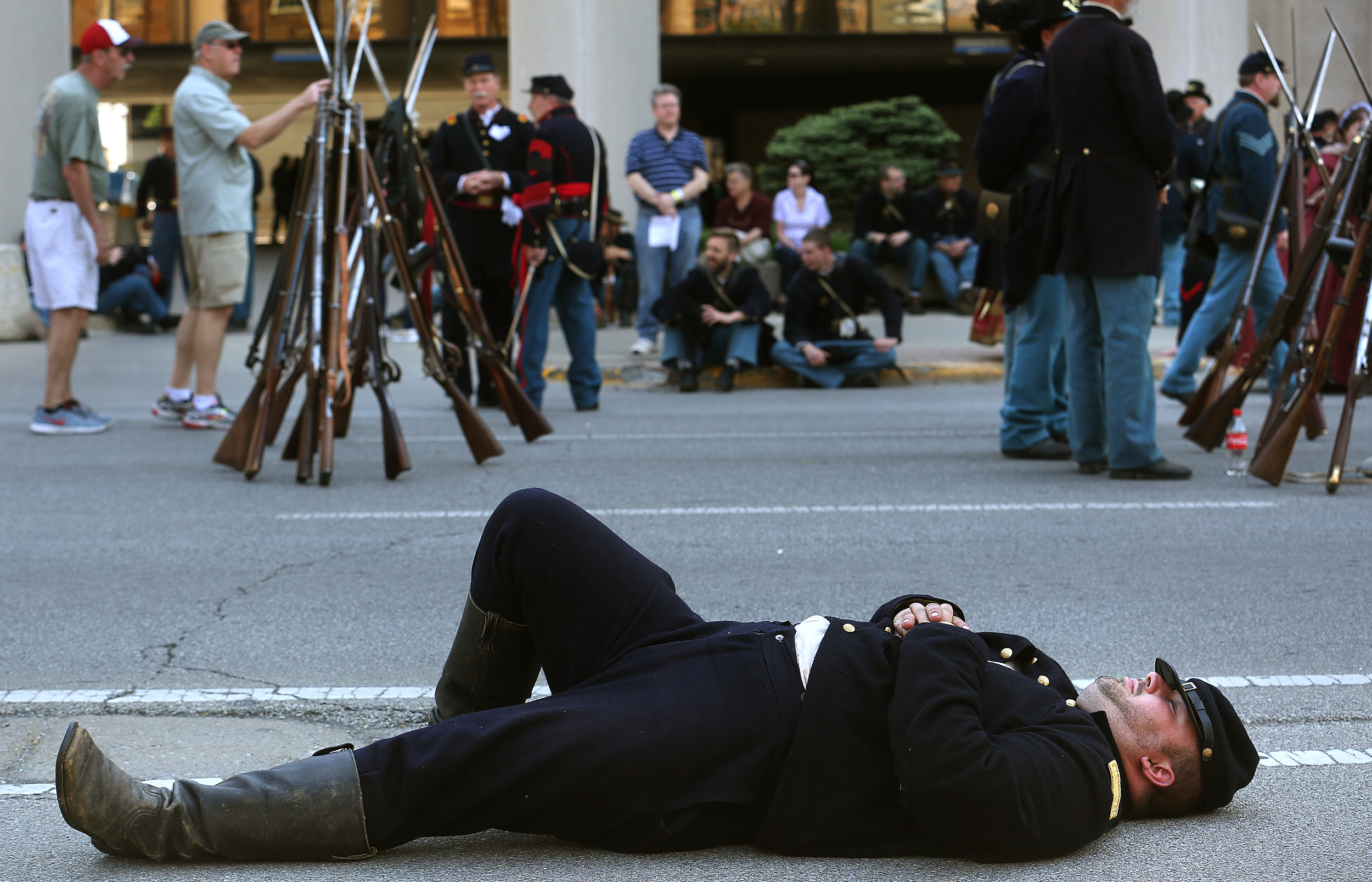 Alex Timmerman, a member of Company B of the Ninth Illinois Regiment from Deer Creek, Ill.,stretches out on Sixth StreetSundaybefore the start of the procession. Timmerman said his company, made up of 21 Union soldiers, had been marching all weekend. David Spencer/The State Journal-Register