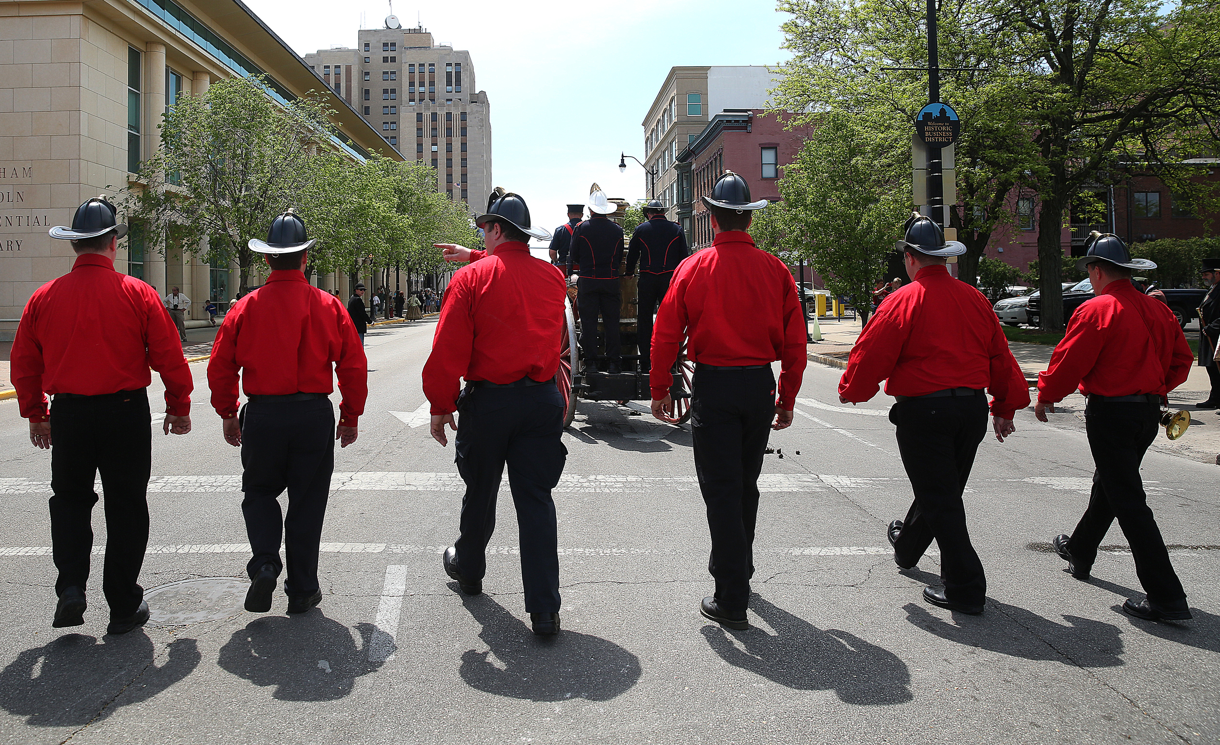 Active duty Springfield firefightersand one retiree,dressed in period red shirts, walk together in thefuneral procession accompanying avintage 1891 fire engine pumper.David Spencer/The State Journal-Register