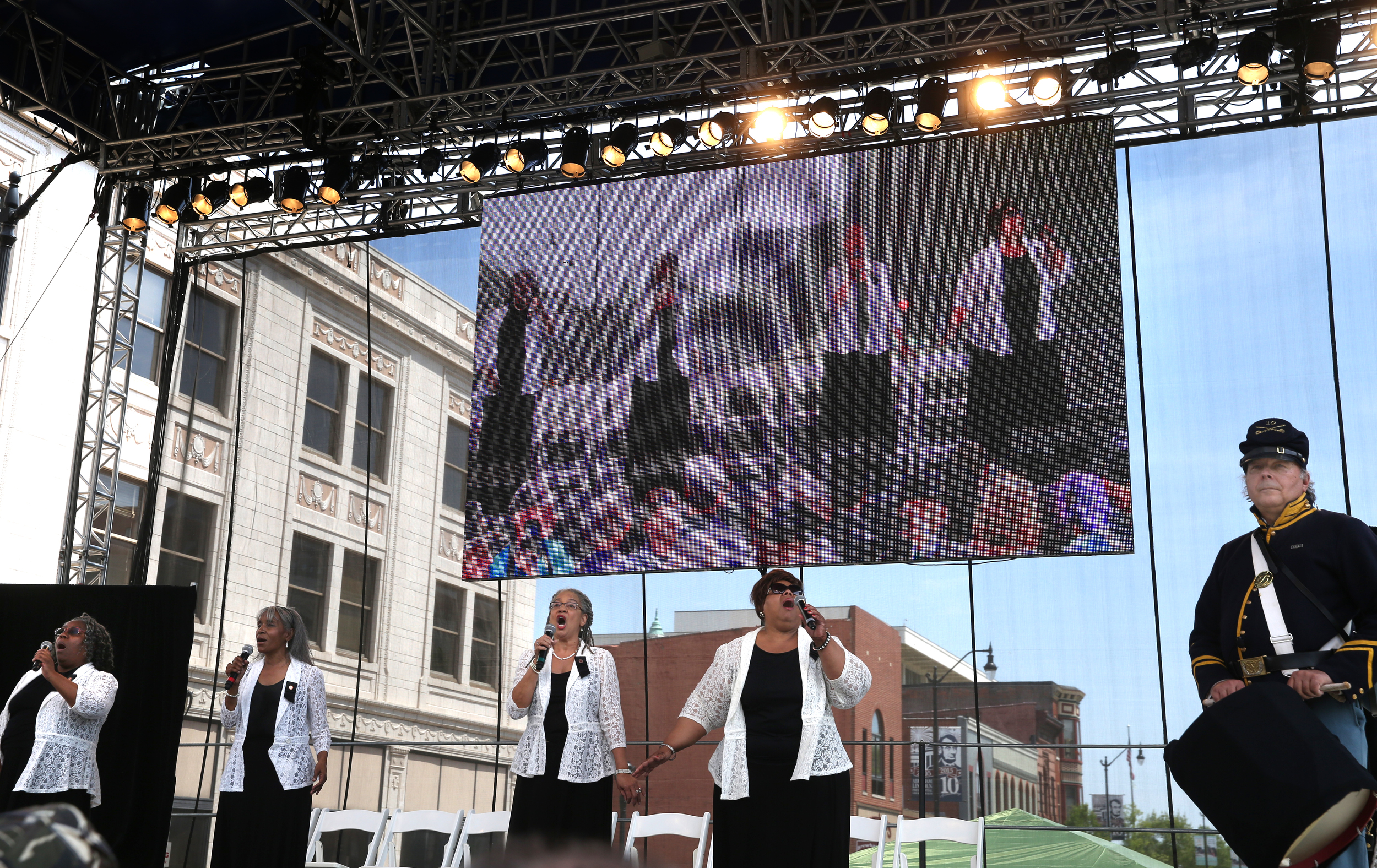 """The Four Sopranos, a Springfield-based gospel quartet made up from left to right: Neyna Johnson, Tracie Shaw, Paula Irby, and Esther Davis sing """"The Battle Hymn of the Republic"""" onstage downtown on Sixth St. before the Lincoln coffin was placed into the hearse for the final procession to Oak Ridge Cemetery Sunday afternoon. David Spencer/The State Journal-Register"""