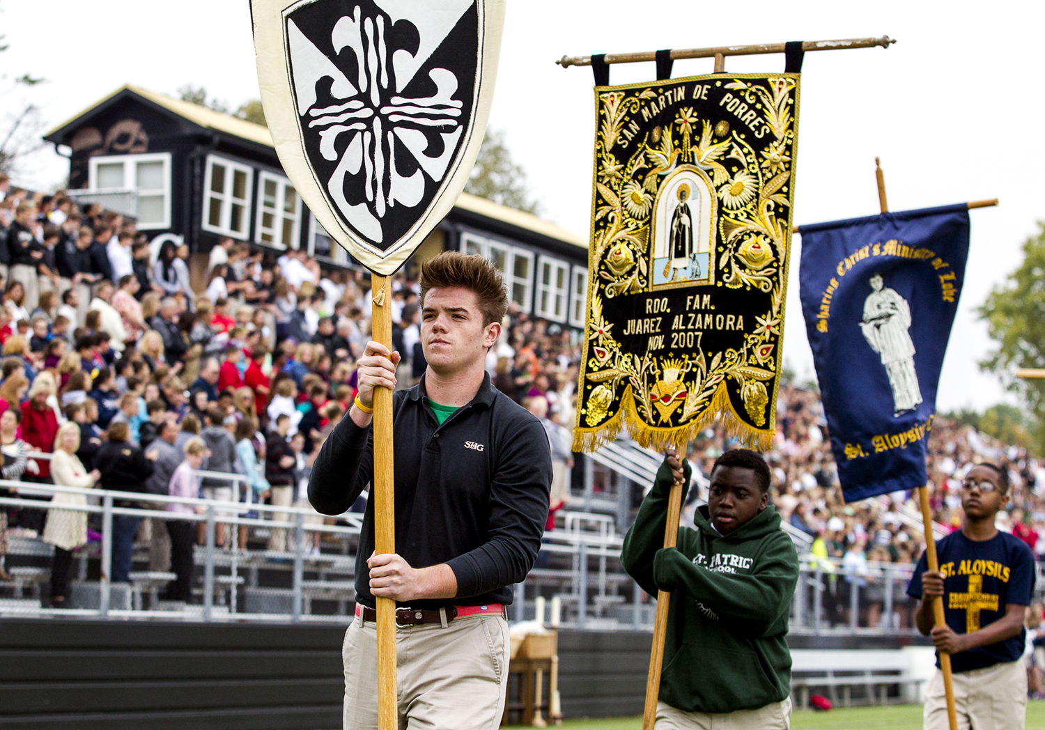 Sacred Heart-Griffin junior Sharky Martin, center, and St. Patrick's fifth grader Ashton Bacon, right, represent their schools as they march across the field during the All City Catholic Schools Mass at the Sacred Heart-Griffin Sports Complex, Monday, Oct. 5, 2015, in Springfield, Ill. The Mass gathers students from the city Catholic schools and was lead by Bishop Thomas Paprocki delivering a message of how the students can lift each other up to help everyone succeed. Justin L. Fowler/The State Journal-Register