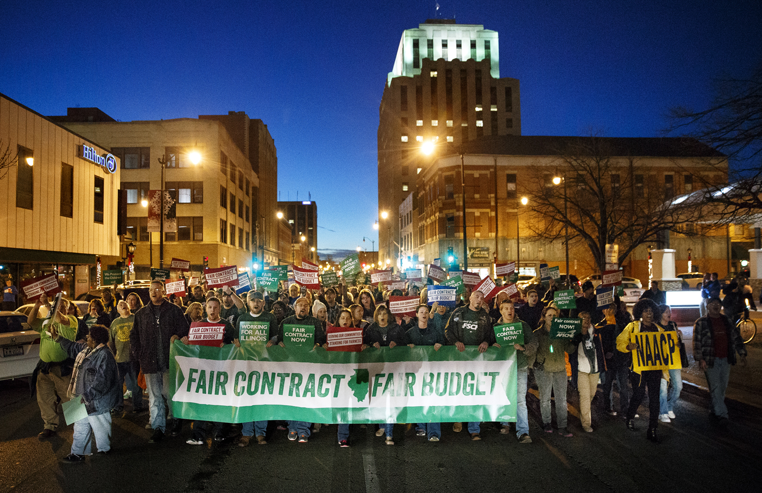 """Demonstrators chant and wave signs as they make their way down Adams Street to the Prairie Capital Convention Center to participate in one of the American Federation of State, County and Municipal Employees' seven statewide """"Rallies for Fairness"""" Thursday, Dec. 10, 2015. Ted Schurter/The State Journal-Register"""