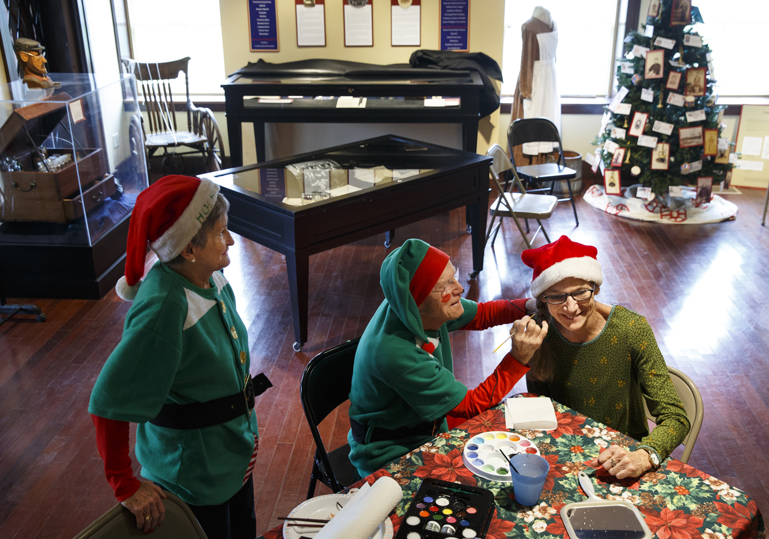 """Ann Gay watches as her husband Farrell paints a snowman on Sue Massie's cheek in the basement of the Elijah Illes house during the """"An Historic Christmas"""" program presented at seven different Springfield historic sites Saturday, Dec. 12, 2015. Ted Schurter/The State Journal-Register"""