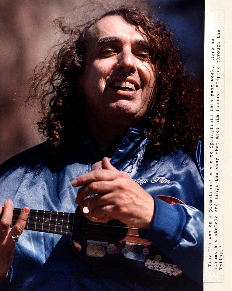 """Several days after I did this portrait of Tiny Tim singing """"Tiptoe Through the Tulips"""" to me on the Old State Capitol Plaza during his promotional visit to Springfield in late March 1990, I received perhaps the most bizarre but complimentary phone call ever from the ukelele strumming celebrity. Calling from New York City- a point he emphasized, Tim told me this was the best photo ever taken of himself-or something to that effect. He then went on to say he wanted to order about 500 reprints and that his agent would be in touch to work out the details: a follow-up phone call that never materialized.David Spencer/The State Journal-Register"""