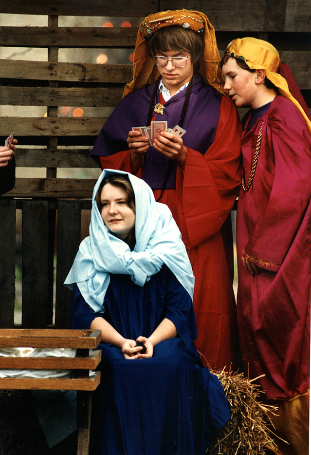 """The reality of adolescence was on display in this photo titled """"Wise guys"""" which appeared along with the following caption in the SJR in early December, 1993: """"One of the attractions at the annual Carlinville Christmas Market on the Carlinville square Sunday was a live nativity display performed by the seventh and eighth-grade Sunday school class of The Federated Church. Standing around for 30 minutes wore down the attention span of some of the youngsters. To bide their time, several took up a friendly game of cards. Wise man Tom Drury checks his hand while fellow wise man Steve Schmitt looks on. Mary, portrayed by Katie Graham, sits next to the manger -- oblivious to the action going on behind her."""" David Spencer/The State Journal-Register"""