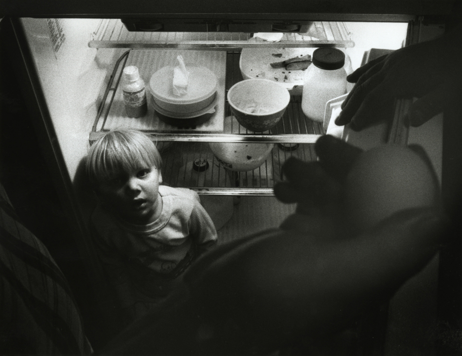 """In the fall of 1990 for a story on rural hunger in the midst of some of the most fertile farmland in the world, I photographed the Nolting family of Modesto. Here, after the family returned from the Palmyra Food Bank, two-year-old Joseph watches as his mom Ann places eggs in the family refrigerator. My original caption for this photo reads in part: """"As can be seen, their fridge is practically empty since the Nolting diet is largely boxed and canned goods."""" (the two bags of groceries from the food bank contained six boxes of cereal)David Spencer/The State Journal-Register"""