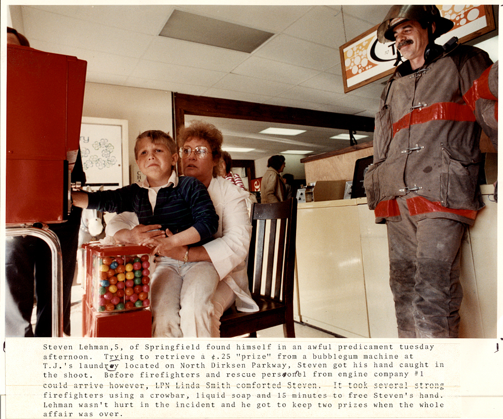 """In re-reading my original typed caption for this April, 1990 photograph in which five-year-old Steven Lehman waits for his hand to be dislodged from the chute of a gumball machine, I realized I spelled it """"shoot"""" instead of chute. So I apologize for the confusion after 27 years. See my original caption above, and read about the happy outcome. David Spencer/The State Journal-Register"""