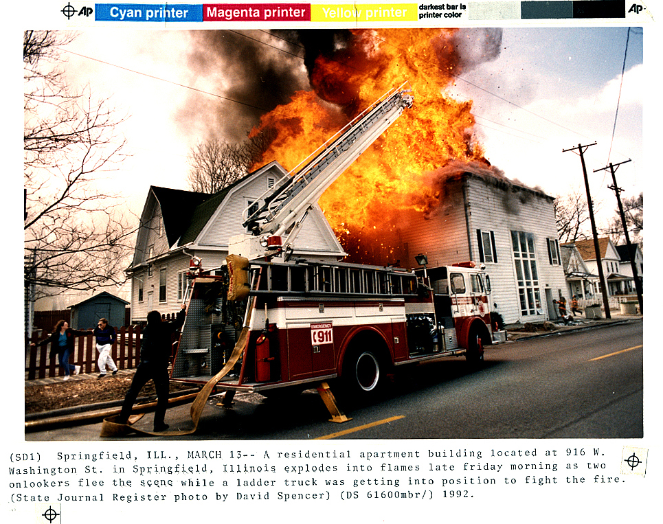 Four Springfield firefighters were injured and this apartment building was destroyed in a March 13, 1992 fire in which the roof of 916 W. Washington St. exploded in a fireball. Two onlookers flee at far left of frame and a Springfield firefighter shields himself behind a fire engine during the blaze. The conflagration was deemed worthy enough to send on the Associated Press wire, with this being the original transmitted photograph. David Spencer/The State Journal-Register