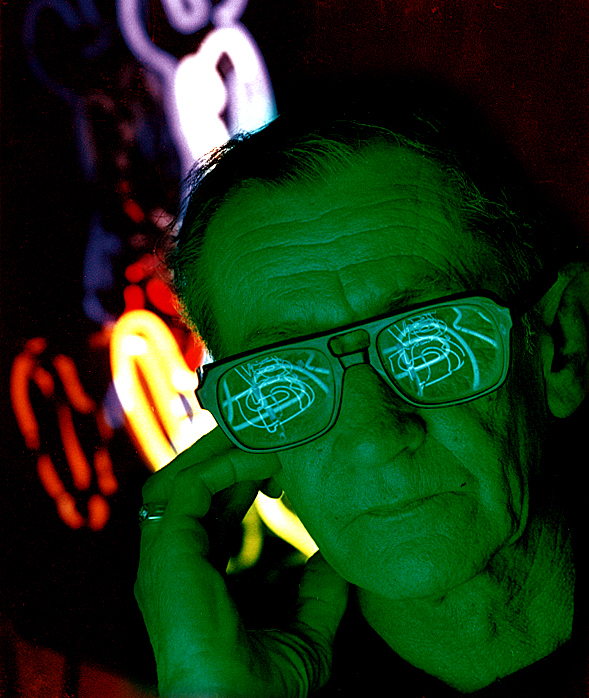 """Neon sign maker Joel Lohr (1927-2010) is bathed in the green glow of one of his creations while surrounded by signs in progress at his Hillsboro business in early 1992. The photo was used as the cover artwork for a story I did on the art of neon for Heartland magazine titled: """"Neon is a Gas"""" and published April 17, 1992. David Spencer/The State Journal-Register"""