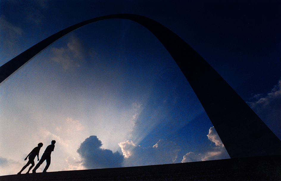 """In 1990, I did a 25th anniversary story on the completion of the Gateway Arch in St. Louis. In this photo, two silhouetted visitors make their way up stairs to the arch in early October of that year. The defining symbol of the city of St. Louis, the arch was designed in 1947 by Finnish-American architect Eero Saarinen. Clad in stainless steel, it is 630 feet tall and was built (according to Wikipedia) """"in the form of an inverted, weighted catenary arch"""". The entry continues that """"it is the world's tallest arch, the tallest man-made monument in the Western Hemisphere, and Missouri's tallest accessible building. Built as a monument to the westward expansion of the United States, it is the centerpiece of the Jefferson National Expansion Memorial."""" David Spencer/The State Journal-Register"""