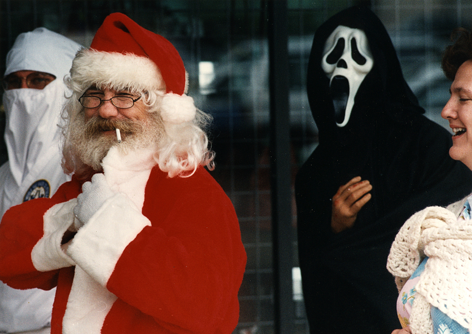 """While at another assignment at Springfield's Town & Country Shopping Center I ran into this festive group I believe were heading to a lunchtime Halloween party. This unpublished photograph taken in late October, 1993 features Santa Claus taking a drag on his cigarette followed behind by Ghostface from Scream movie fame. (the character at that time was known as """"The Peanut-Eyed Ghost"""", with Scream being released in late 1996) David Spencer/The State Journal-Register"""