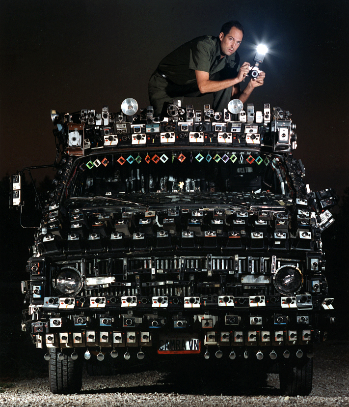 """Taken at a rest stop on I-55 outside Springfield, artist and filmmaker Harrod Blank sits on the roof of his famous creation: the """"Camera Van"""", for a feature I did on art cars in the fall of 1995. Featuring over 2000 cameras attached to the exterior (and interior as well) of a 1972 Dodge, the van had recently left Blank's native California earlier that Spring, and was heading south to its' next adventure down the interstate in Illinois after I had photographed this most unusual vehicle at the inaugural Chicago Art Car parade several days earlier.David Spencer/The State Journal-Register"""