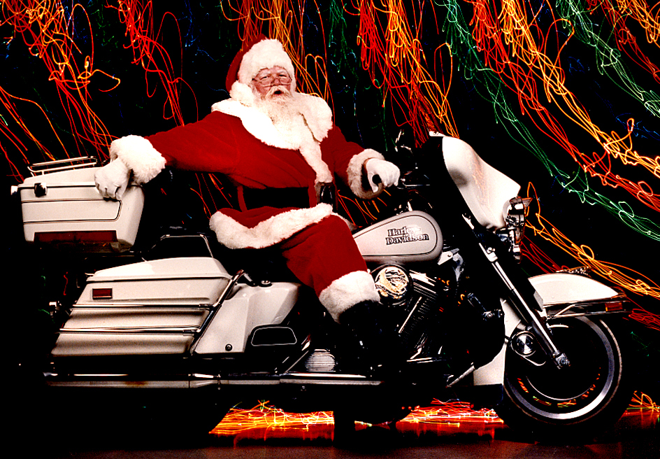 """The biggest challenge of photographing Springfield's Bill Bosie, (1939-2002) a legendary Santa Claus around these parts, was getting his trusty sidekick Harley Davidson motorcycle safely into our third-floor photo studio. With just a few fits and starts, the job was accomplished by yours truly, along with a time exposure involving the movement of elongated strands of colored lights to fill in the background area while the camera shutter was held open for a December, 1992 feature. Our story noted why Bosie was so beloved by area children, an empathy that should be required of everyone wearing the jolly red suit: """"The worst part of the job is when you visit with a kid who has nothing and you know isn't going to get anything -- I hate that,"""" Bosie says. """"I get a big kick out of it when they believe. Really believe. You can see it in their eyes."""" David Spencer/The State Journal-Register"""