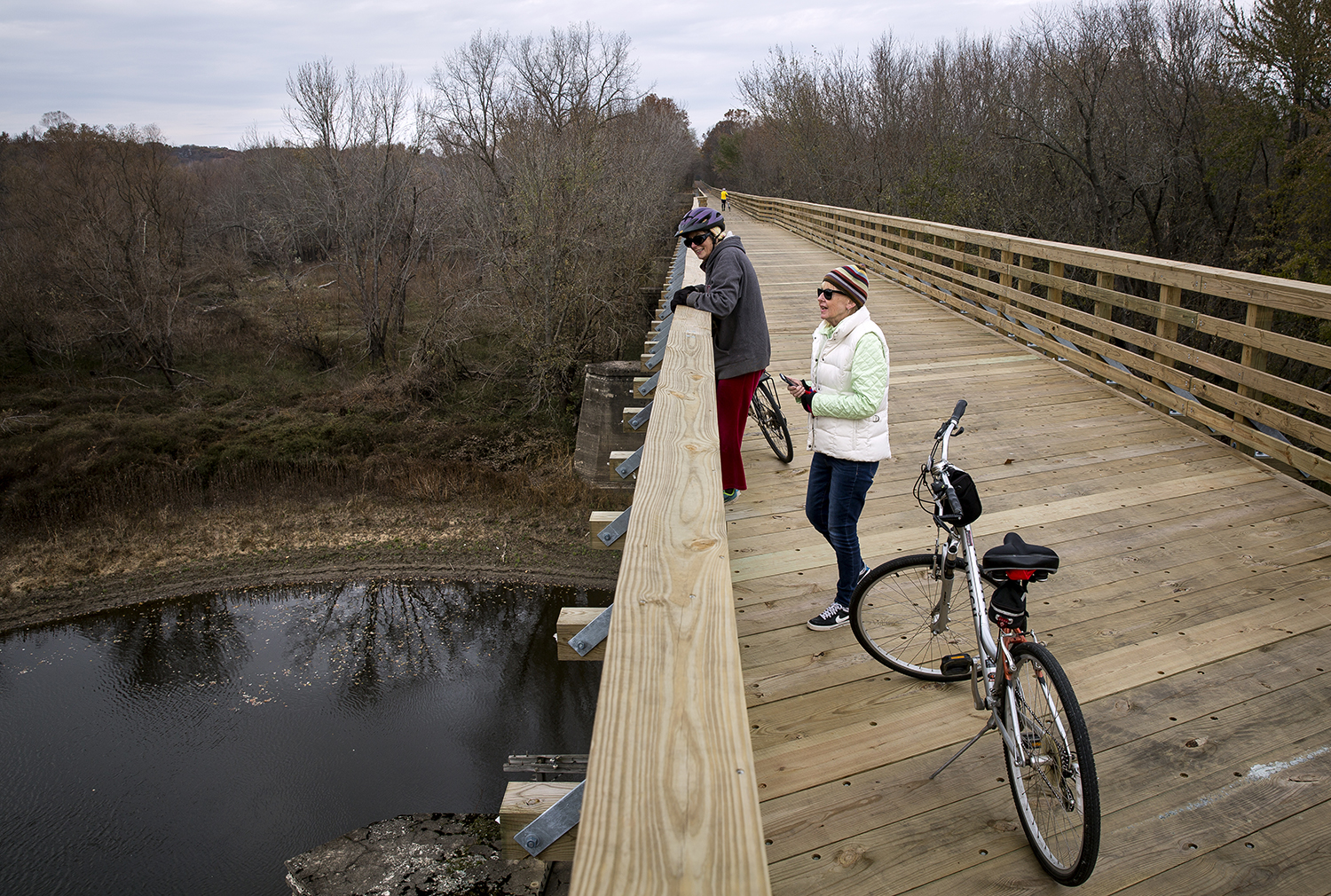 Therese Talmant, left, and Donna Wilson take in the view of the Sangamon River during a bike ride on the Sangamon Valley Trail extension Tuesday, Nov. 14, 2017, in Springfield, Ill. The trail officially opens Thursday with a ribbon cutting ceremony. [Rich Saal/The State Journal-Register]