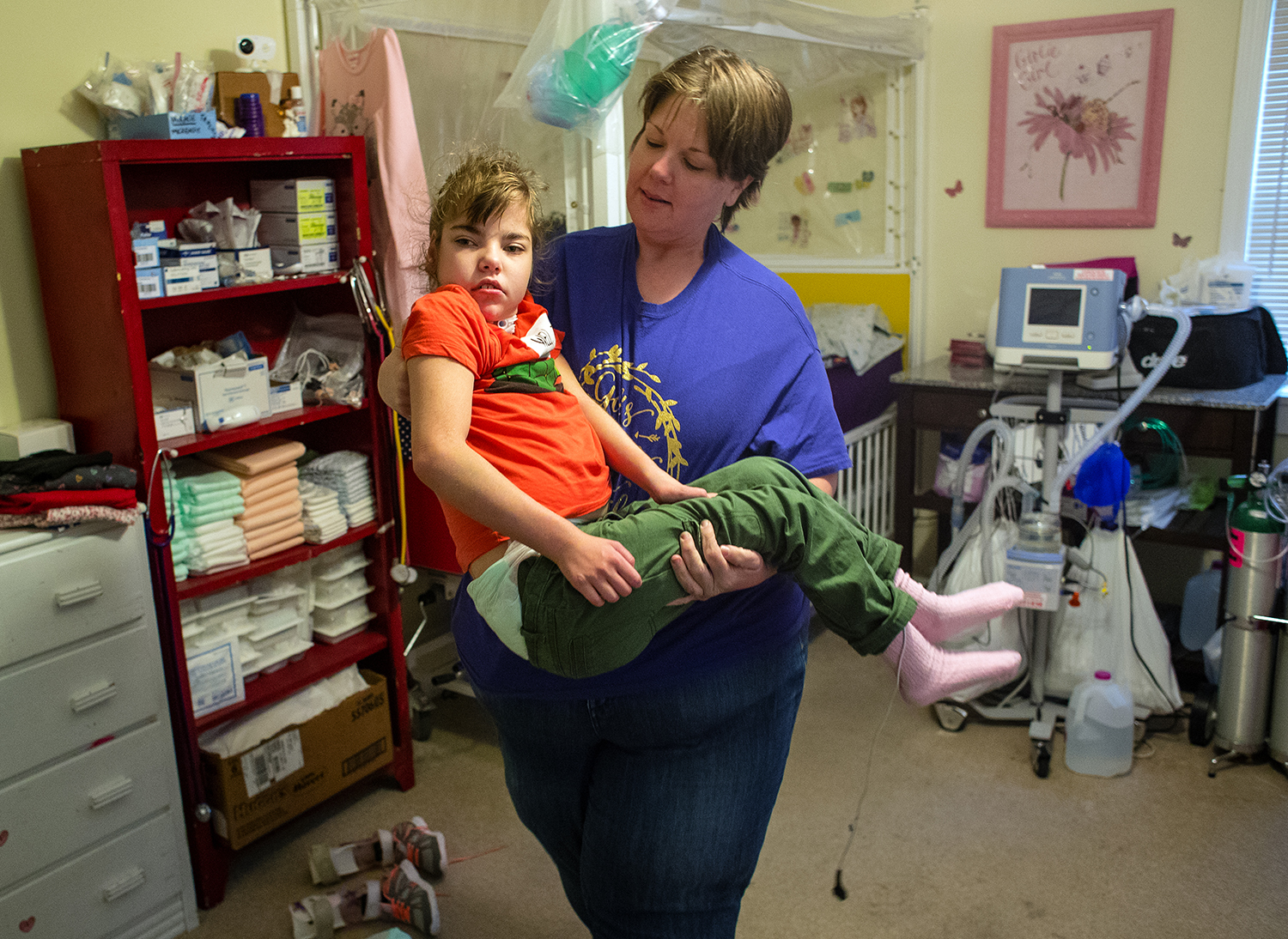 Rebekah Strate carries her 9-year-old daughter McKenzie to her wheelchair in her Murrayville home Friday, Nov. 17, 2017. Strate said she is worried that she will lose her children's current durable medical equipment provider, Memorial Home Services, if a company hired to reboot Illinois' Medicaid managed-care program makes significant cuts in payments for medical equipment. Strate is raising two children with complex medical needs who use equipment to keep them breathing. [Ted Schurter/The State Journal-Register]