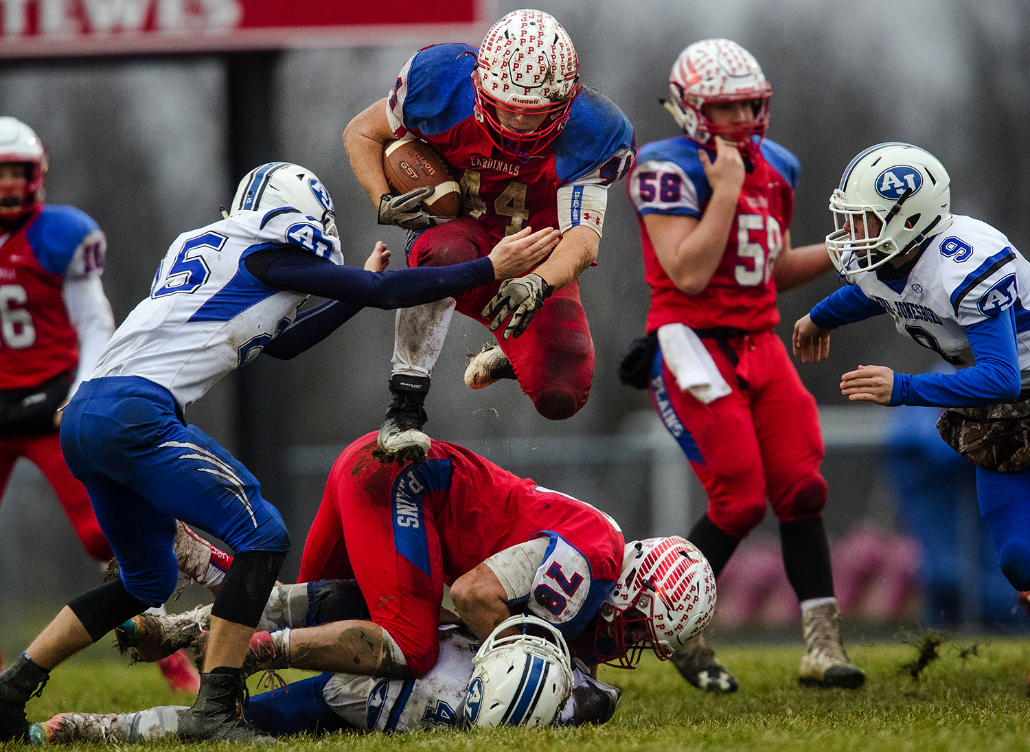 Pleasant Plains' Nik Samson leaps over a teammate and a Anna-Jonesboro defender as he picks up a few of his 209 yards rushing during the IHSA Class 3A football semifinal game at Pleasant Plains High School Saturday, Nov. 18, 2017. [Ted Schurter/The State Journal-Register]