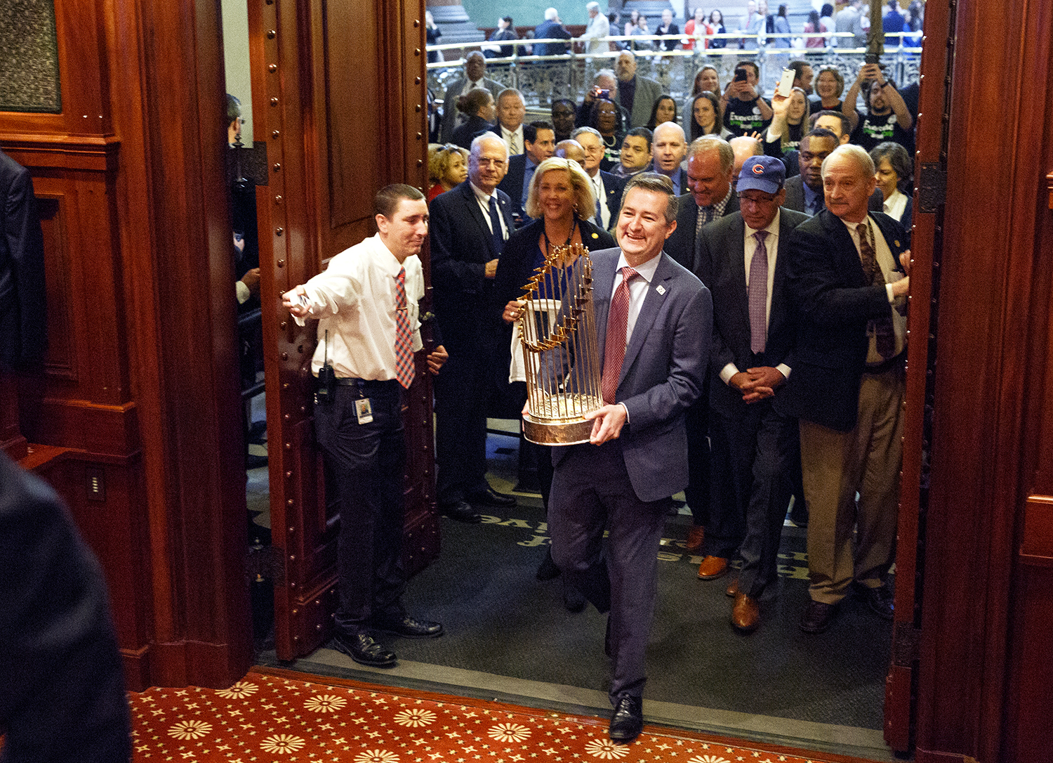 Chicago Cubs Chairman Tom Ricketts carries the Cubs' World Series trophy into the House chamber March 8 at the Capitol. The World Champion Chicago Cubs were honored during a joint session of the General Assembly. Rich Saal/The State Journal-Register