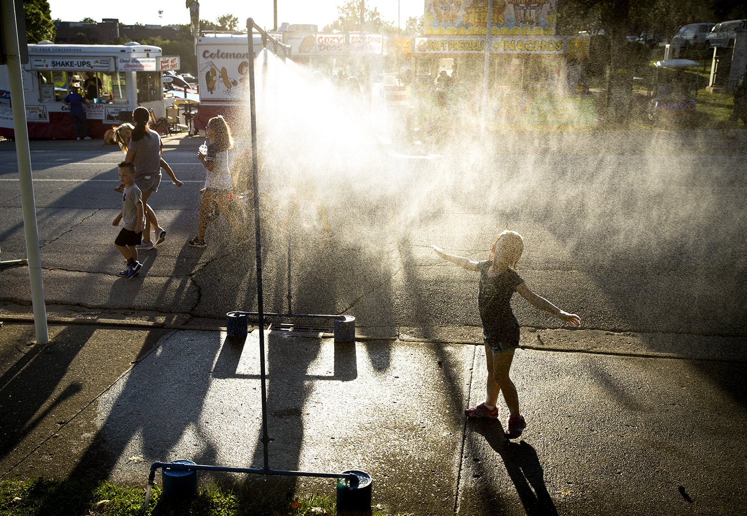 Sophia Jordan, 6, cools off in a mist sprayer at the Illinois State Fair Aug. 17. Rich Saal/The State Journal-Register