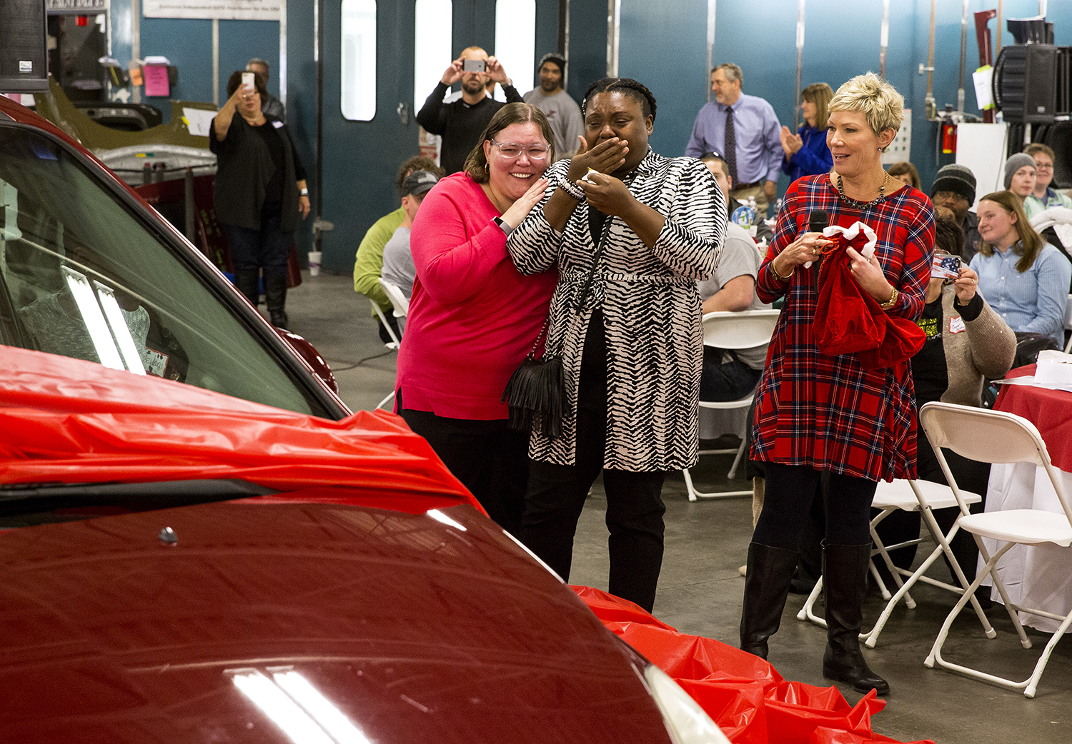 A new car for Alana Yates, center, is unwrapped at Zara's Collision Center Dec. 6 during the business's holiday car give-away luncheon event. With Yates is her friend, Dawn Scheller, left, and Julie Zara. Zara's benevolence program, which is in its 19th year, partners with numerous local businesses to acquire and restore used cars for deserving families. A car was also presented during the event to Jamie Smith and her family. Rich Saal/The State Journal-Register