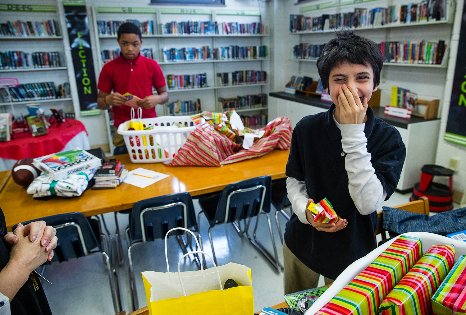 "Daniel Murawski laughs as he realizes the box of candy he just unwrapped from his ""Out of the Blue"" holiday prize basket, is his favorite, Lemonheads, at Jefferson Middle School Dec. 13. Basket distribution began on Dec. 4 and goes through Dec. 15, with five to 12 baskets being given away per day to students who are selected for demonstrating respect of self, others and property. Ted Schurter/The State Journal-Register"