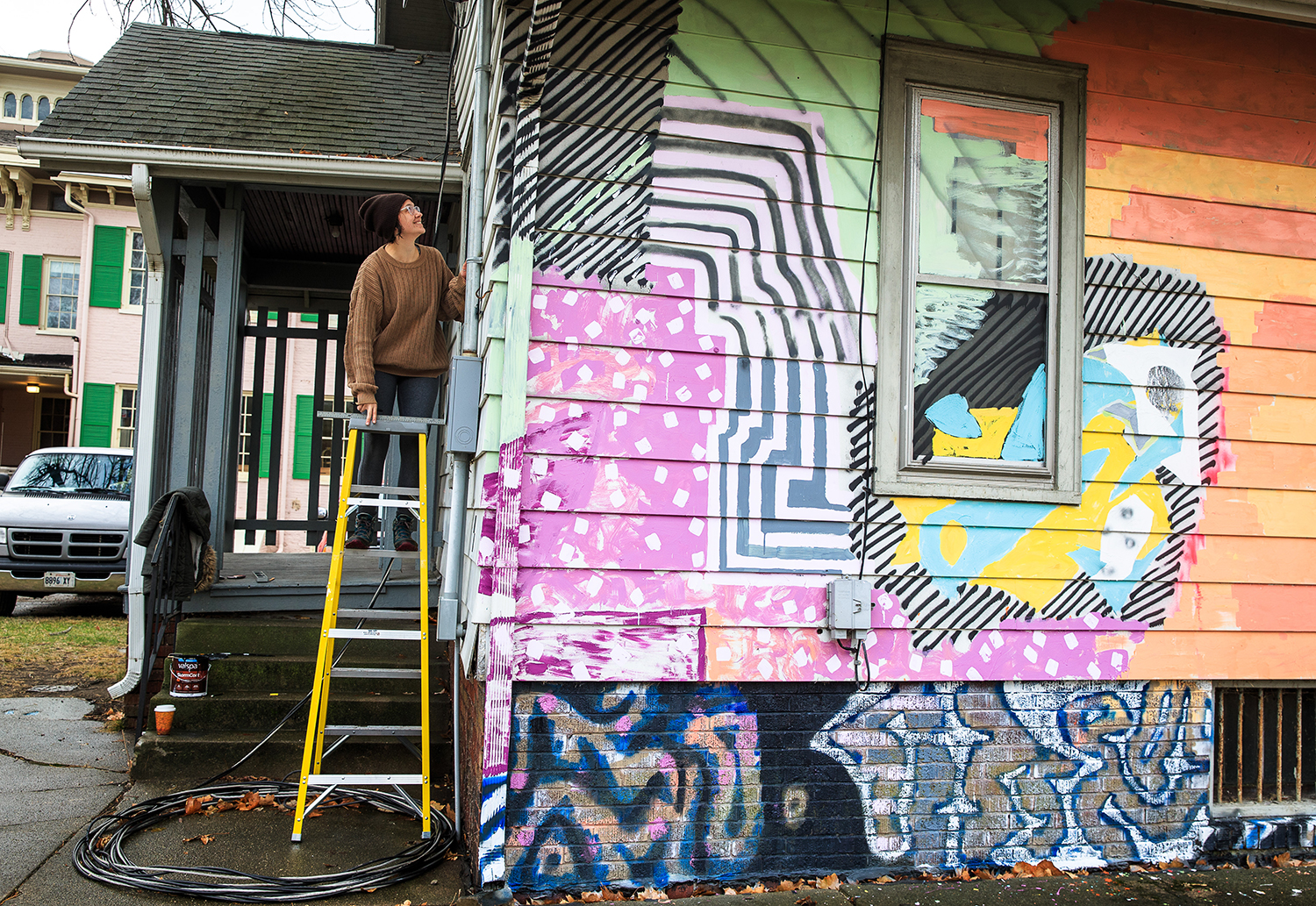 """Grace Katalinich, center, a junior member of the DEMO Project, scales a ladder to draw in the installation of a piece by Tom Burtonwood that includes 3D scanning targets on the rear facade of the The DEMO Project facility, a space donated for use by the Springfield Art Association and directed by artists affiliated with the University of Illinois Springfield, at 732 N. 4th St., Thursday, Jan. 11, 2018, in Springfield, Ill. Burtonwood did 3D scans of the house and used them to create a 3D print for a piece called """"Offset Registration"""" that was an exhibit in the house. The farewell party for the house will be on Saturday Jan. 13th from 2-5 p.m. [Justin L. Fowler/The State Journal-Register]"""